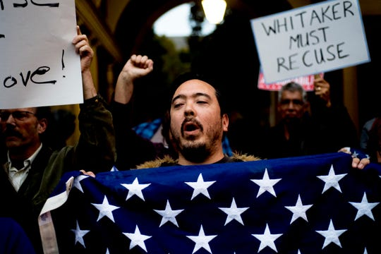 A protester chants while waving an American flag during a protest outside the Federal Courthouse in Knoxville on Thursday.