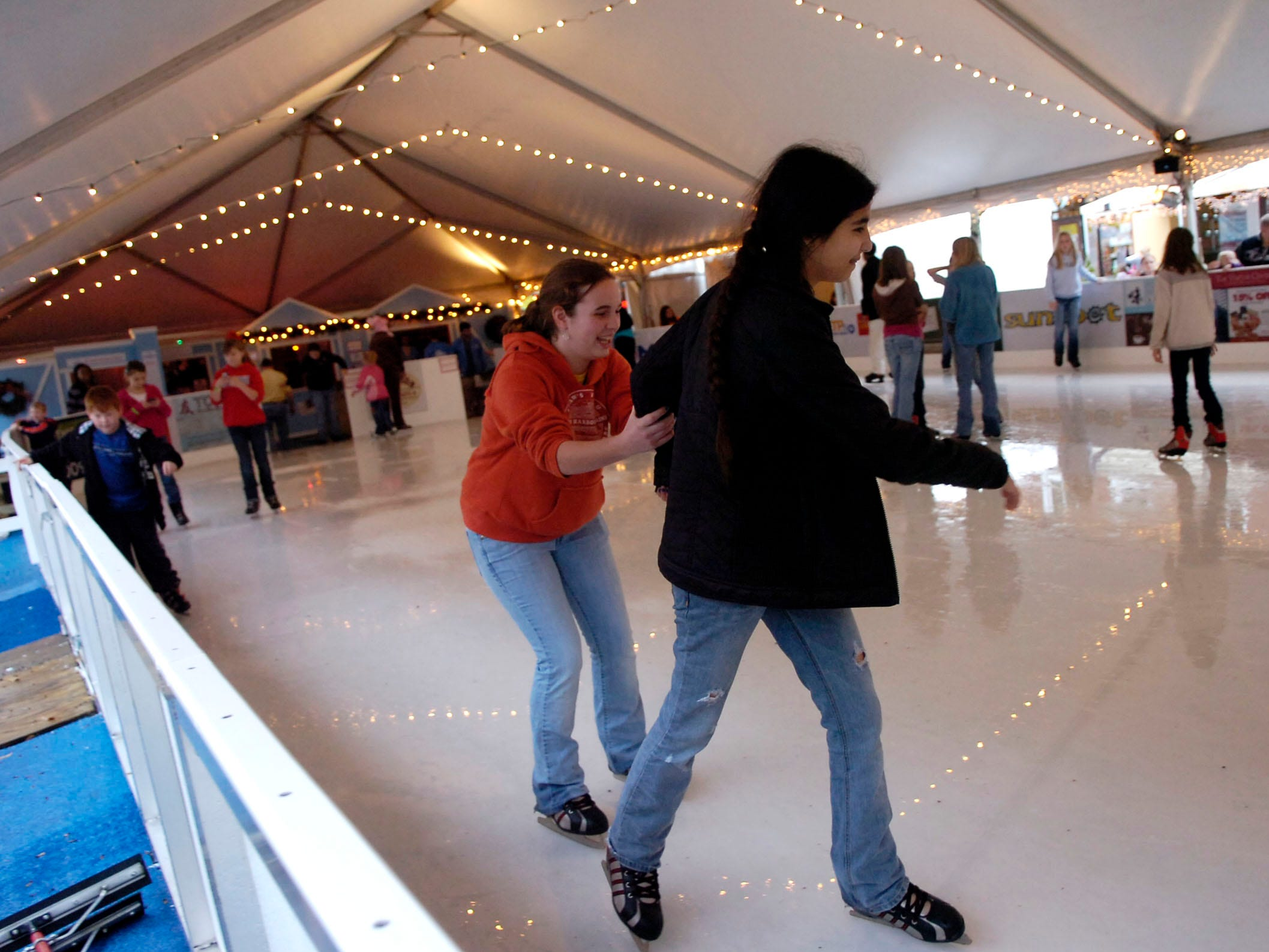 Emma Barns (left) holds on to Gaby Caloca as they skate around the Knoxville Holidays on Ice skating rink on Friday at Market Square in 2008.