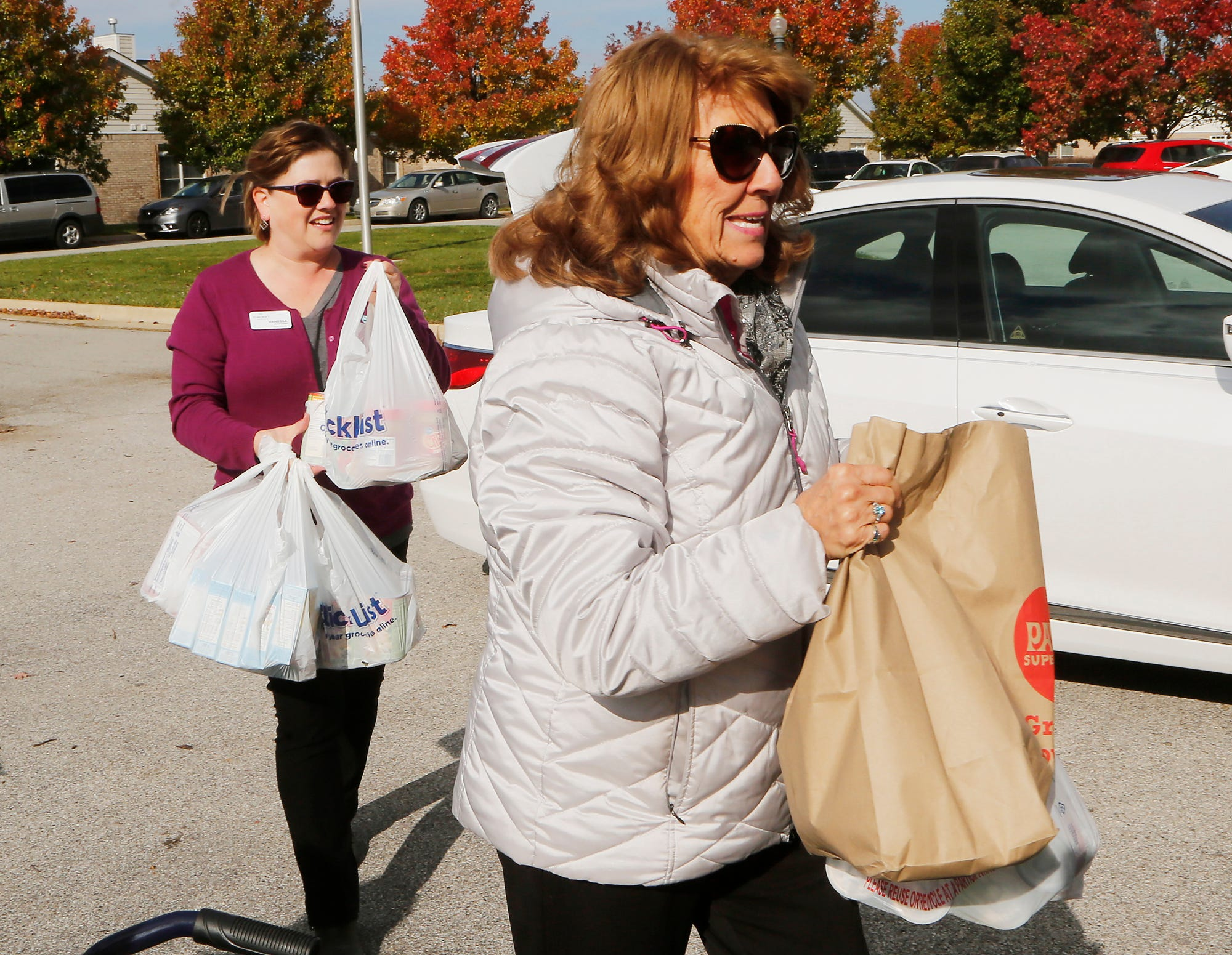 Kay Burry, right, brings several sacks of groceries to help with the Fill the Ambulance Food Drive Thursday, November 8, 2018, at Elmcroft senior living community, 3575 Senior Place in West Lafayette. Burry who is with Soller-Baker Funeral Homes, said everybody in the office participated in food donations. Elmcroft teamed with Phoenix Paramedics Solutions for the food drive to benefit Food Finders Food Bank. Behind Burry is Vanessa Sowders from Elmcroft.