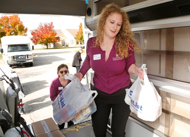 Victoria Gray, foreground, and Vanessa Sowders load bags of donated groceries during the Fill the Ambulance Food Drive Thursday, November 8, 2018, at Elmcroft senior living community 3575 Senior Place in West Lafayette. Elmcroft teamed with Phoenix Paramedics Solutions for the food drive to benefit Food Finders Food Bank. Both Gray and Sowders are with Elmcroft.
