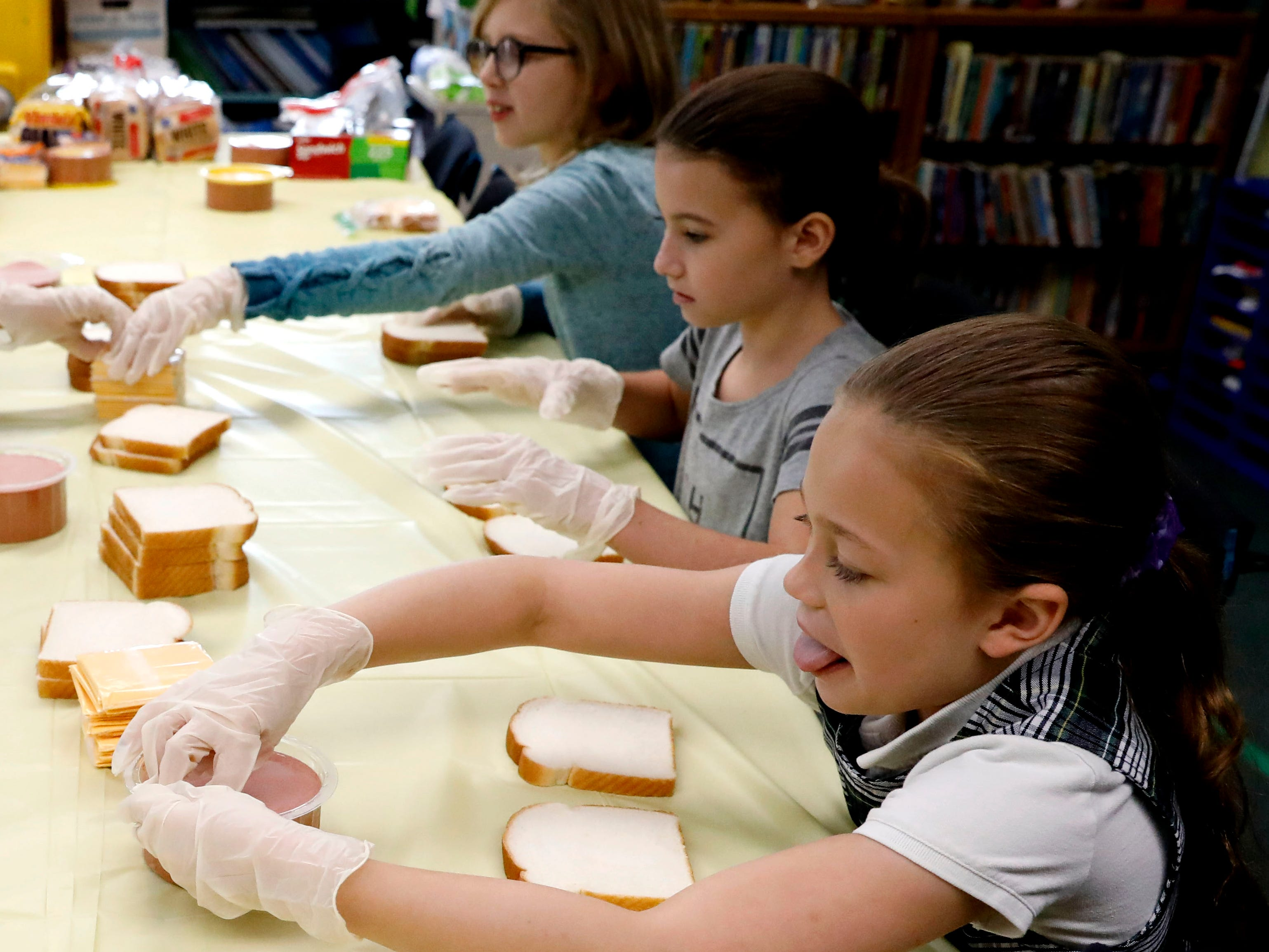 Erica Sharp, right, Zoe DeLeon, center, and Zylie Hopkins make bologna and cheese sandwiches Tuesday, Nov. 8, 2018, at St. Bernadette Catholic School in Lancaster.