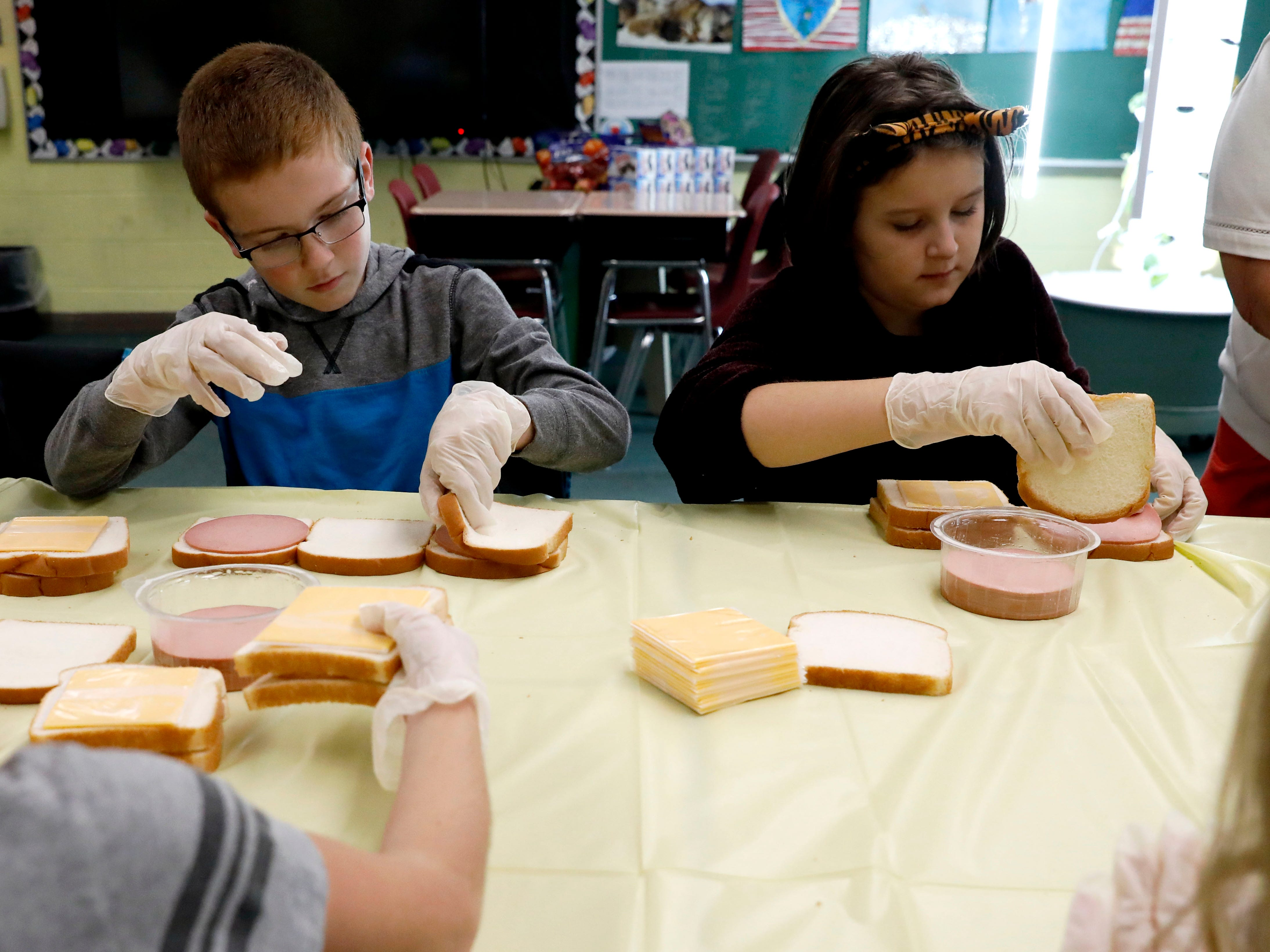 Ethan Schmelzer, left, Ella Fitzgibbon and their fourth grade classmates make bologna and cheese sandwiches Thursday, Nov. 8, 2018, at St. Bernadette Catholic School in Lancaster.