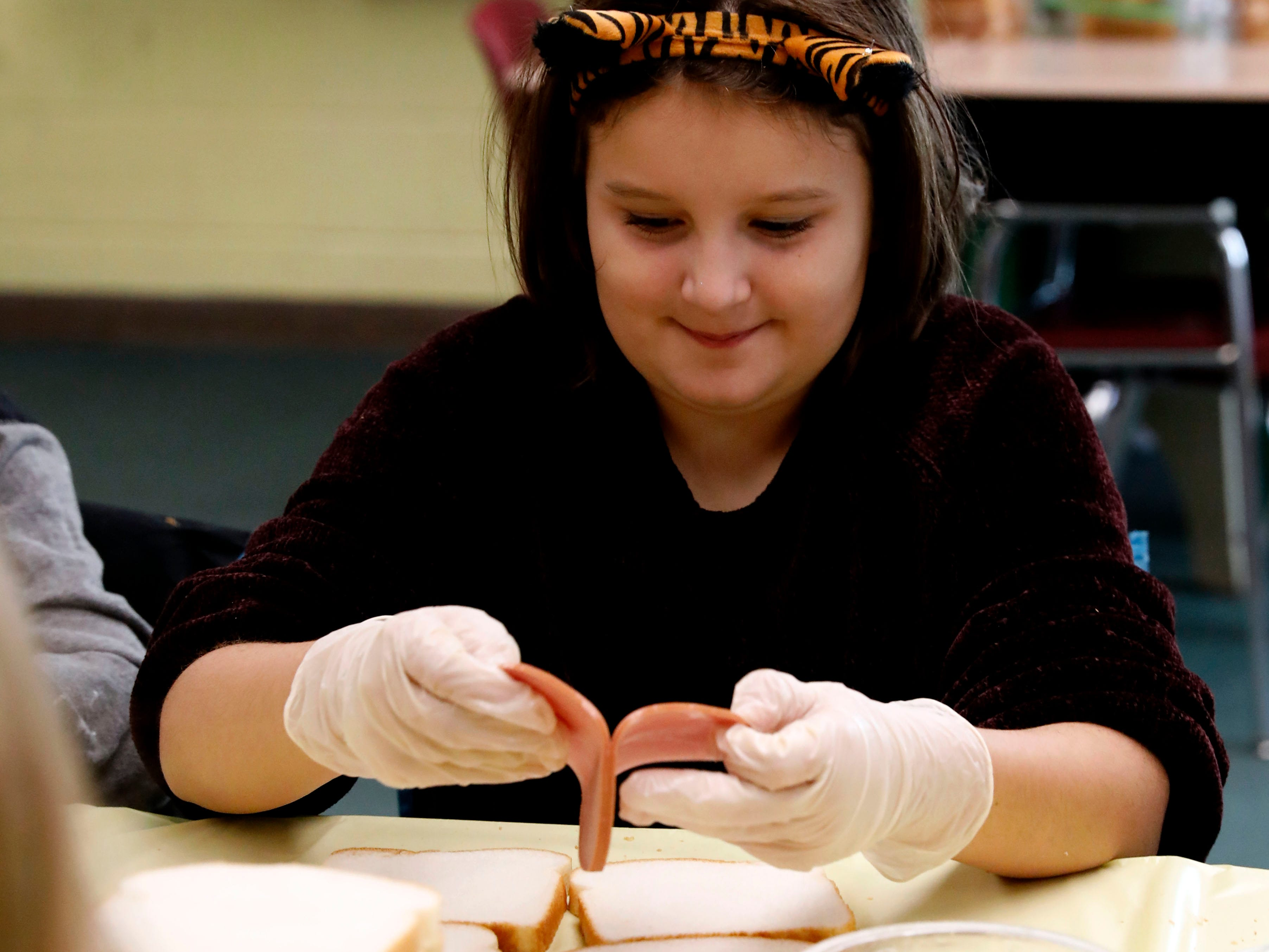 Ella Fitzgibbon peels two pieces of bologna apart from each other Thursday, Nov. 8, 2018, at St. Bernadette Catholic School in Lancaster.