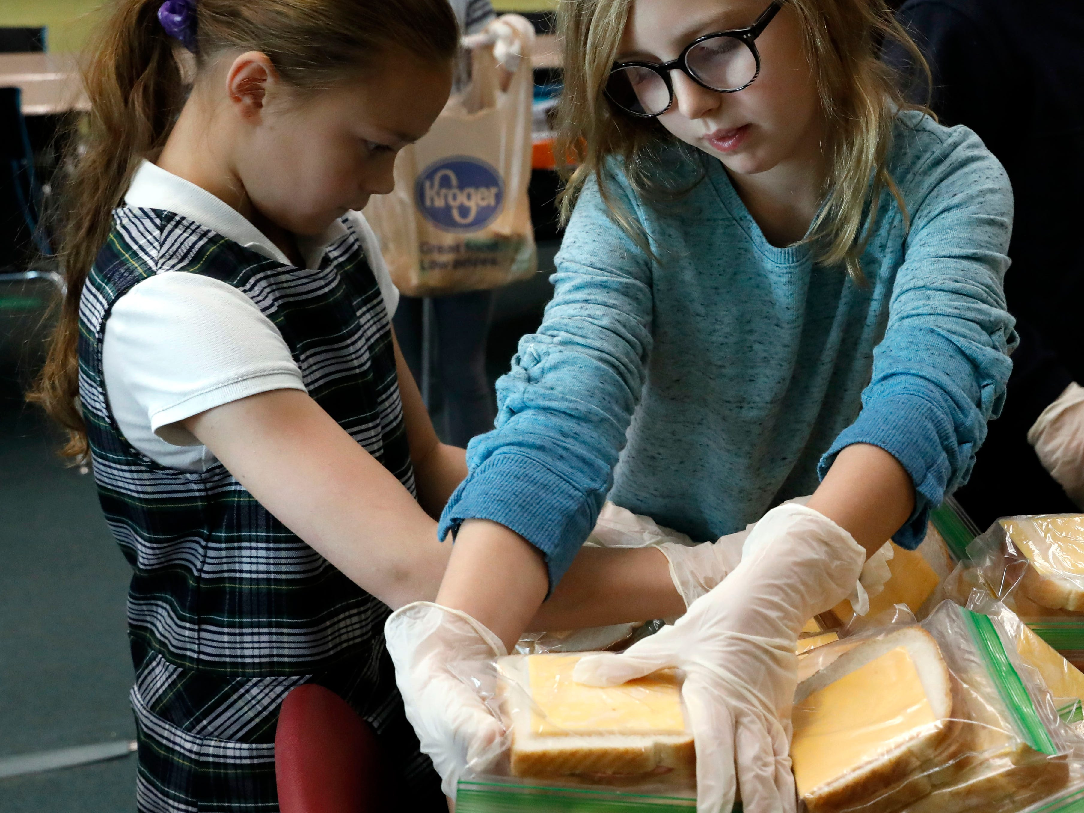 Zylie Hopkins grabs a stack of bologna and cheese sandwiches to bag them up for delivery to Foundation Dinners Thursday, Nov. 8, 2018, at St. Bernadette Catholic School in Lancaster.