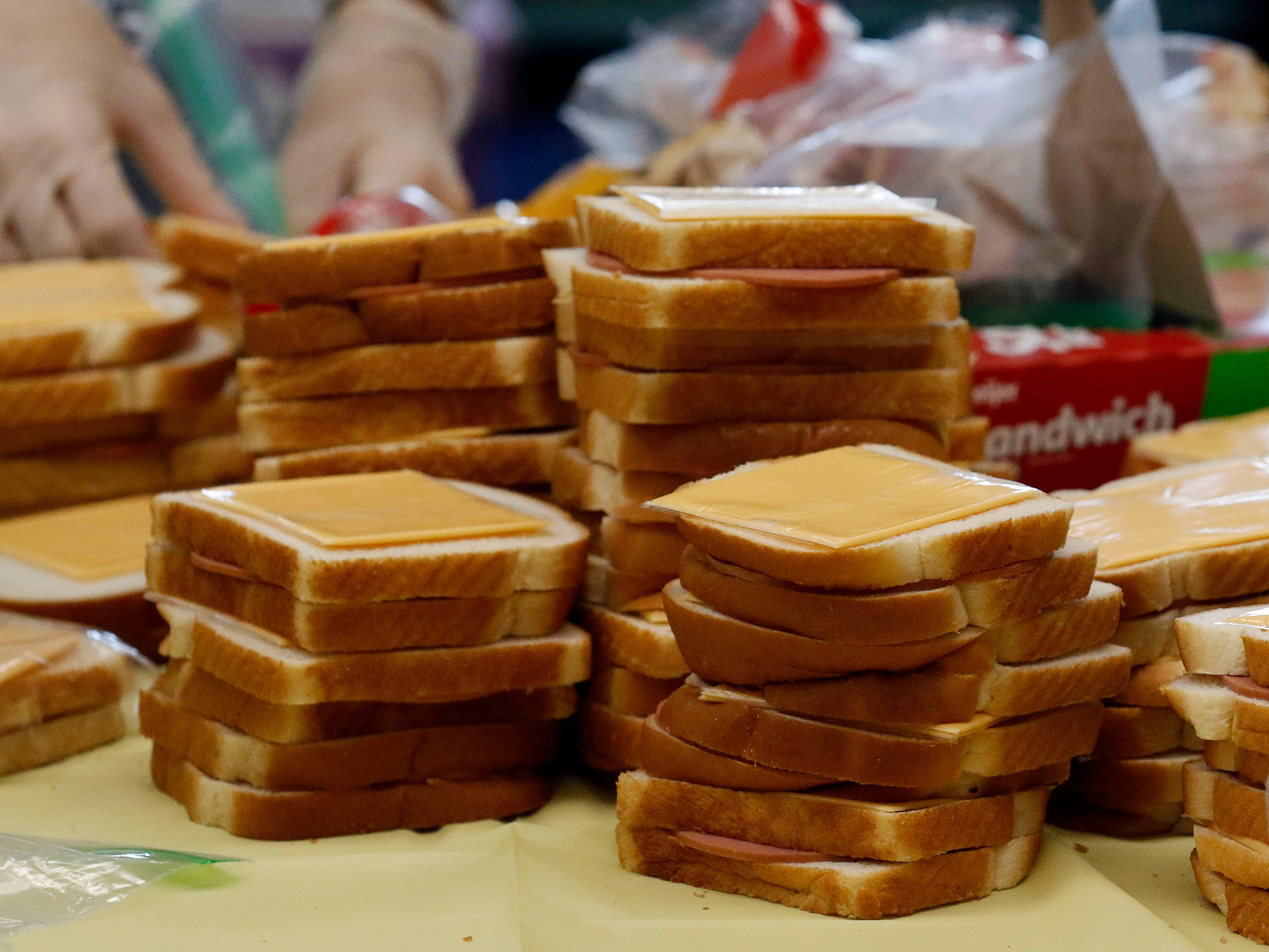 Stacks of bologna and cheese sandwiches wait to be bagged in Robin Sanders's fourth grade classroom Tuesday, Nov. 8, 2018, at St. Bernadette School in Lancaster.