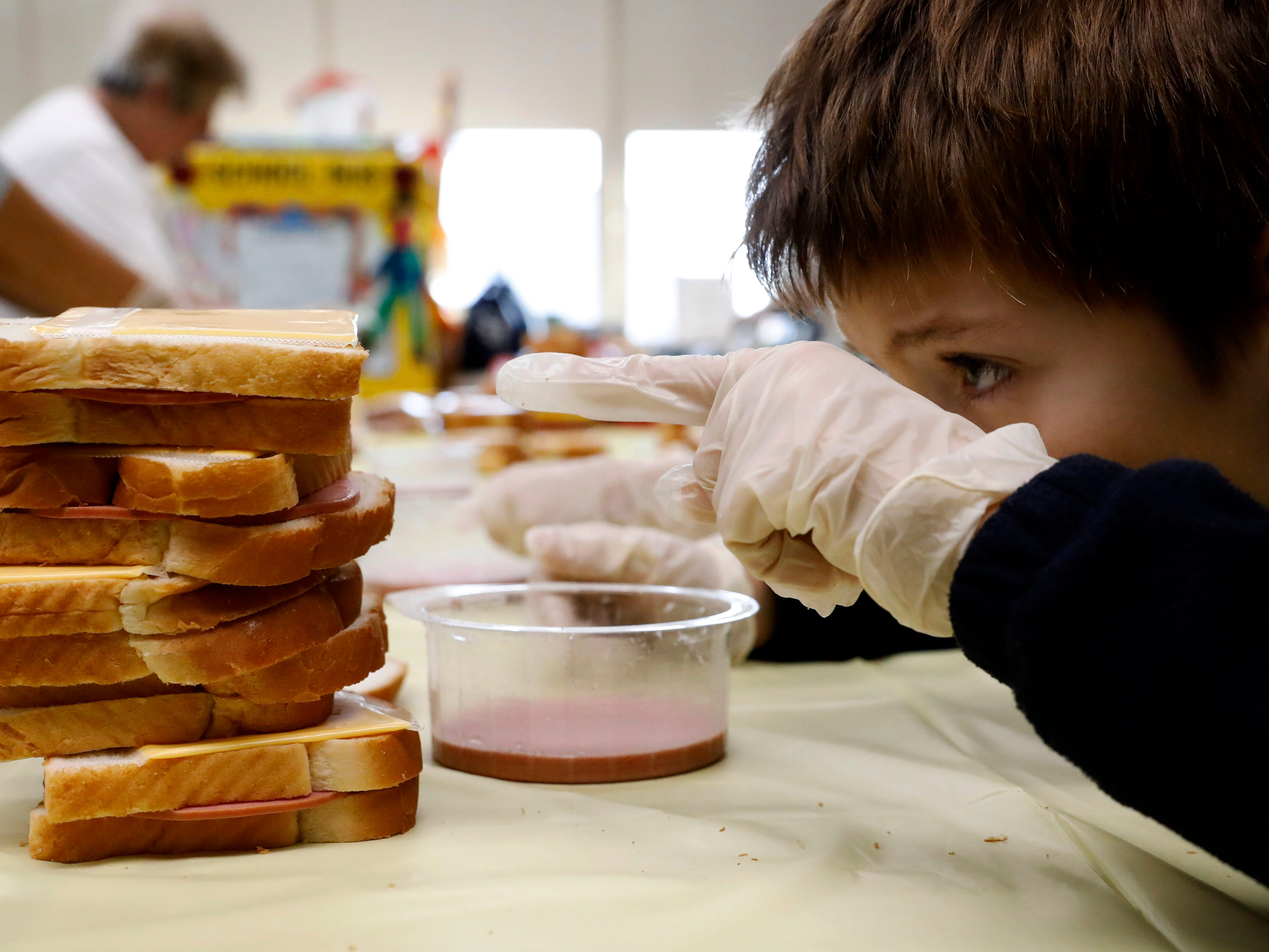 Sam Tencza counts the number of bologna and cheese sandwiches in his stack Thursday, Nov. 8, 2018, at St. Bernadette Catholic School in Lancaster. Every month students at the school make sandwiches for Foundation Dinners in Lancaster. The eight fourth graders at the school made more than 100 sandwiches for the charity to provide to homeless people in Lancaster.