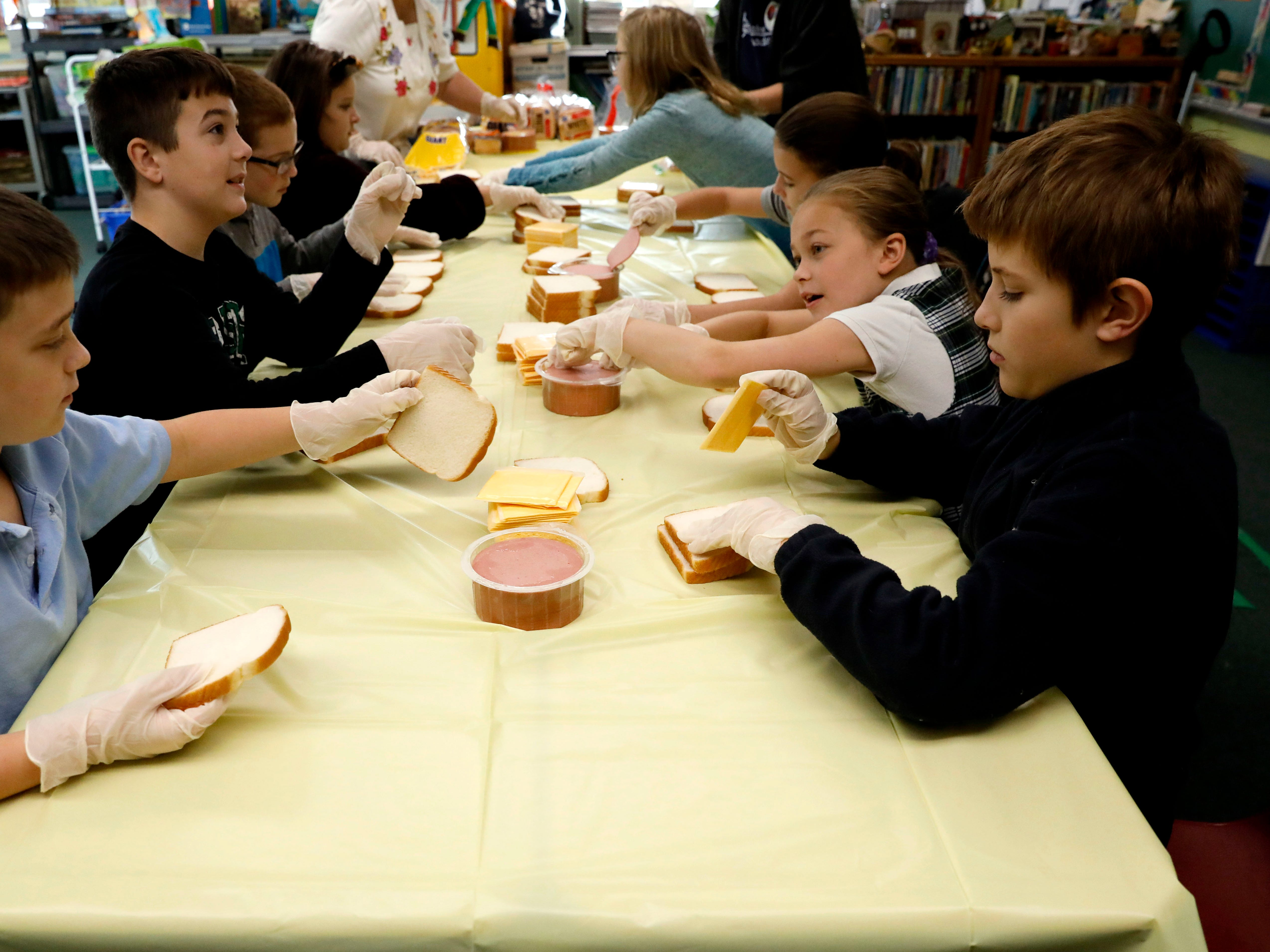 Fourth grade students at St. Bernadette Catholic School make bologna and cheese sandwiches Tuesday, Nov. 8, 2018, for Foundation Dinners in Lancaster.