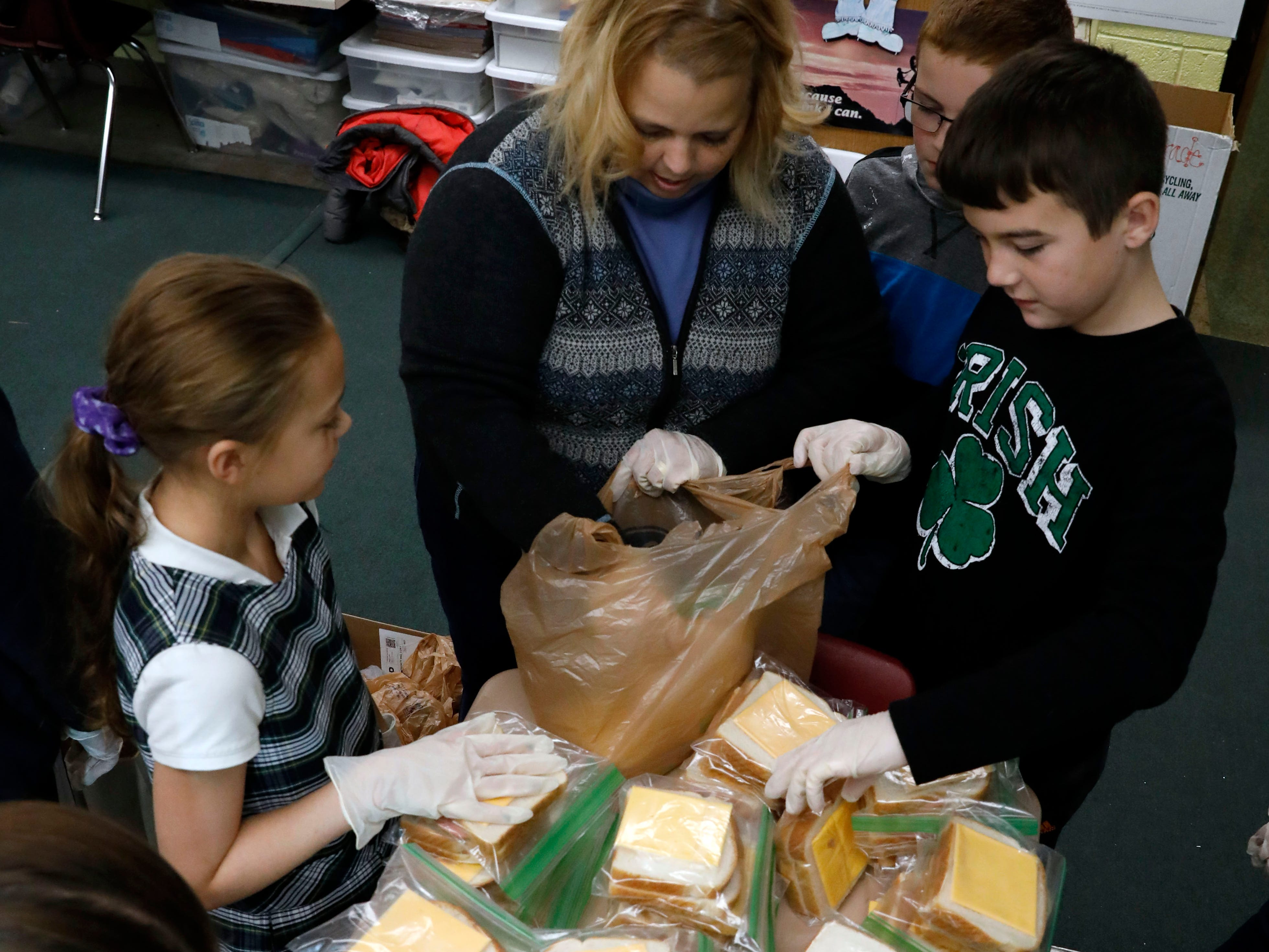 Robin Sanders gets helps her students bag bologna and cheese sandwiches for Foundation Dinners Thursday, Nov. 8, 2018, at St. Bernadette Catholic School in Lancaster.