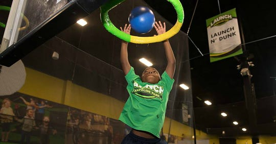 A child dunks a basketball at Launch  Trampoline Park.