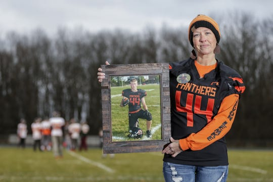 Carrie Holton holds a portrait of her son, Jevon Lemke, on the Reedsville Panthers football field during a practice Wednesday in Reedsville.