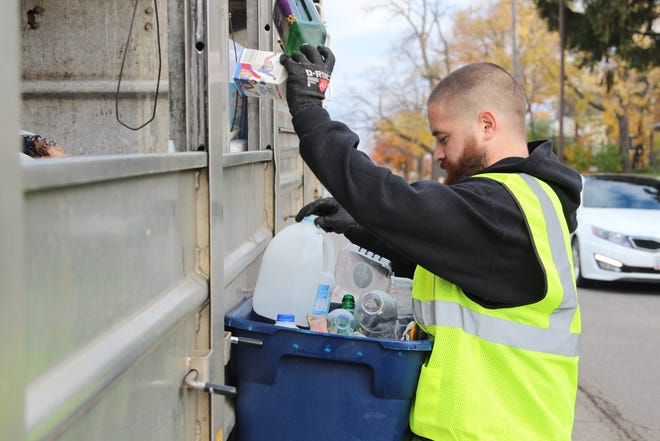 Dustin Larcom, of the city's sanitation and streets department, sorts residents' recycling at the curb. The city is considering no longer picking up curbside recycling.