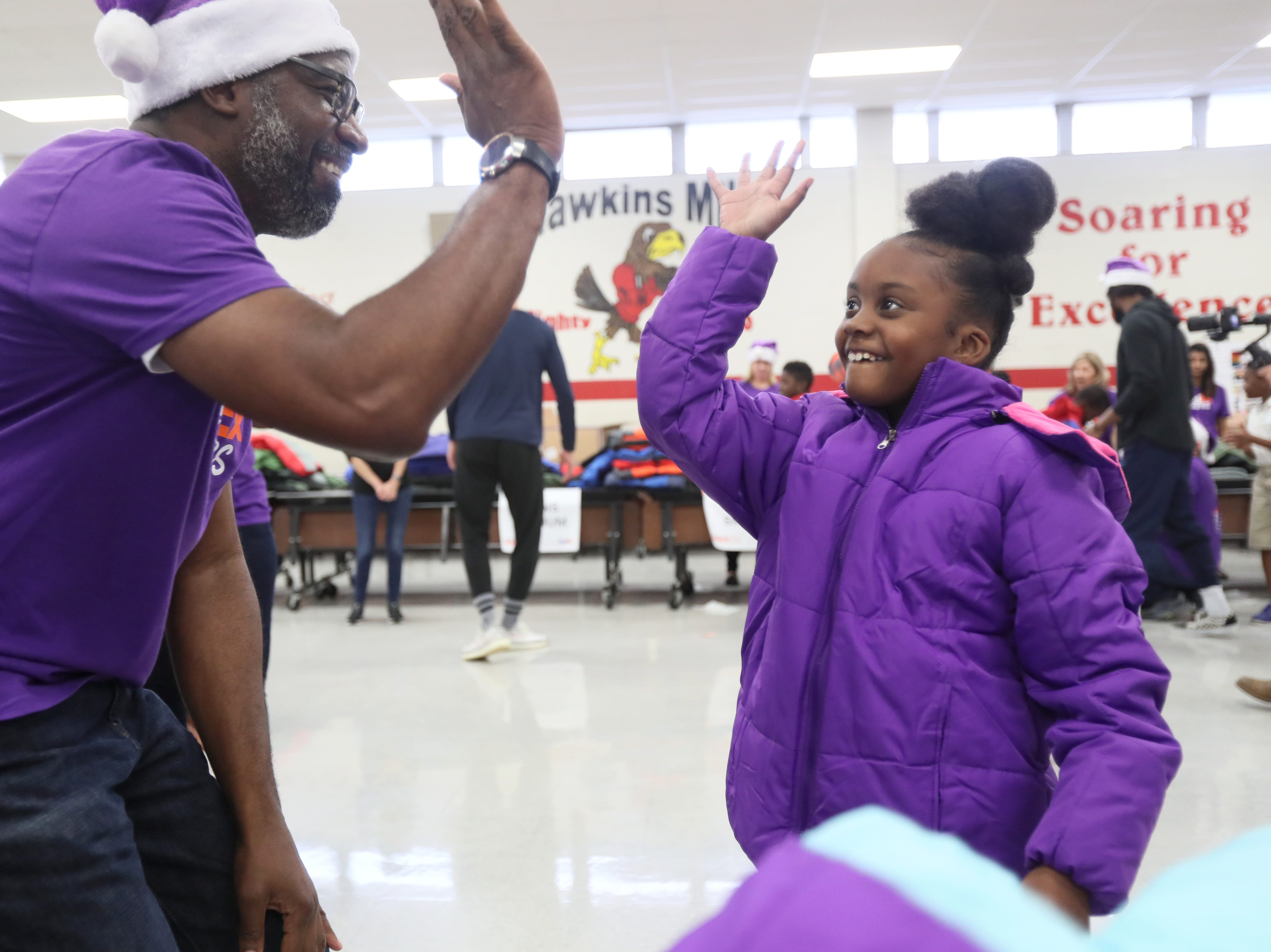Brian Tabor high-fives Ambriella Watson, 9, after helping her find a new coat, as FedEx, the Memphis Grizzlies and Operation Warm surprise children with new winter wear at Hawkins Mill Elementary School on Thursday, Nov. 8, 2018.