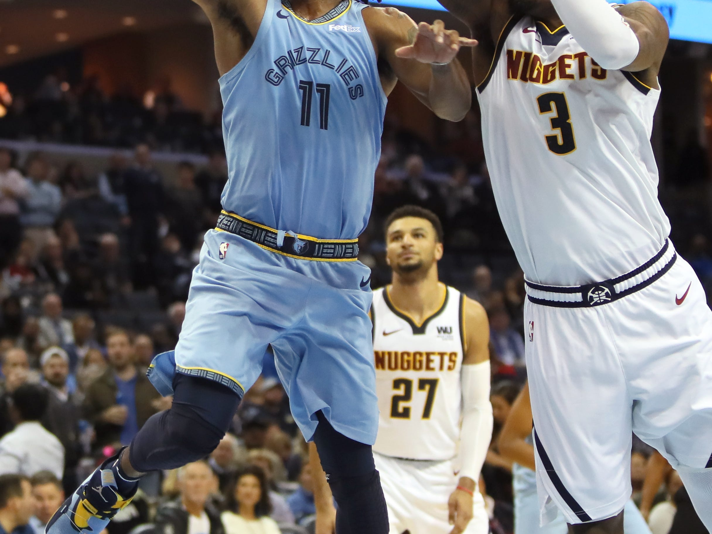 Memphis Grizzlies guard Mike Conley lays the ball up against Denver Nuggets guard Torrey Craig during their game at the FedExForum on Wednesday, November 7, 2018.