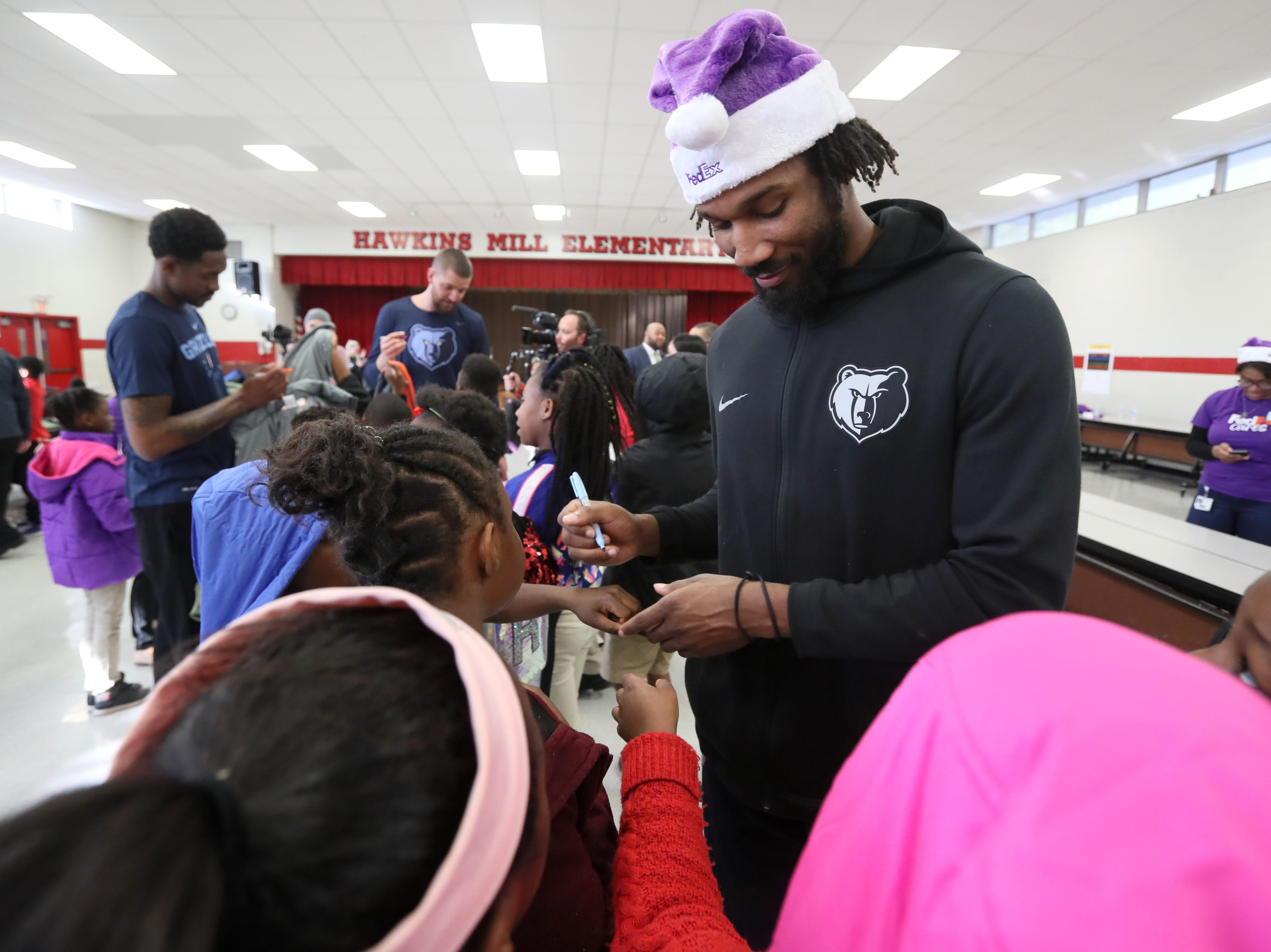 Memphis Grizzlies guard Wayne Selden signs autographs as his team joins FedEx and Operation Warm to help surprise children with new coats at Hawkins Mill Elementary School on Thursday, Nov. 8, 2018.