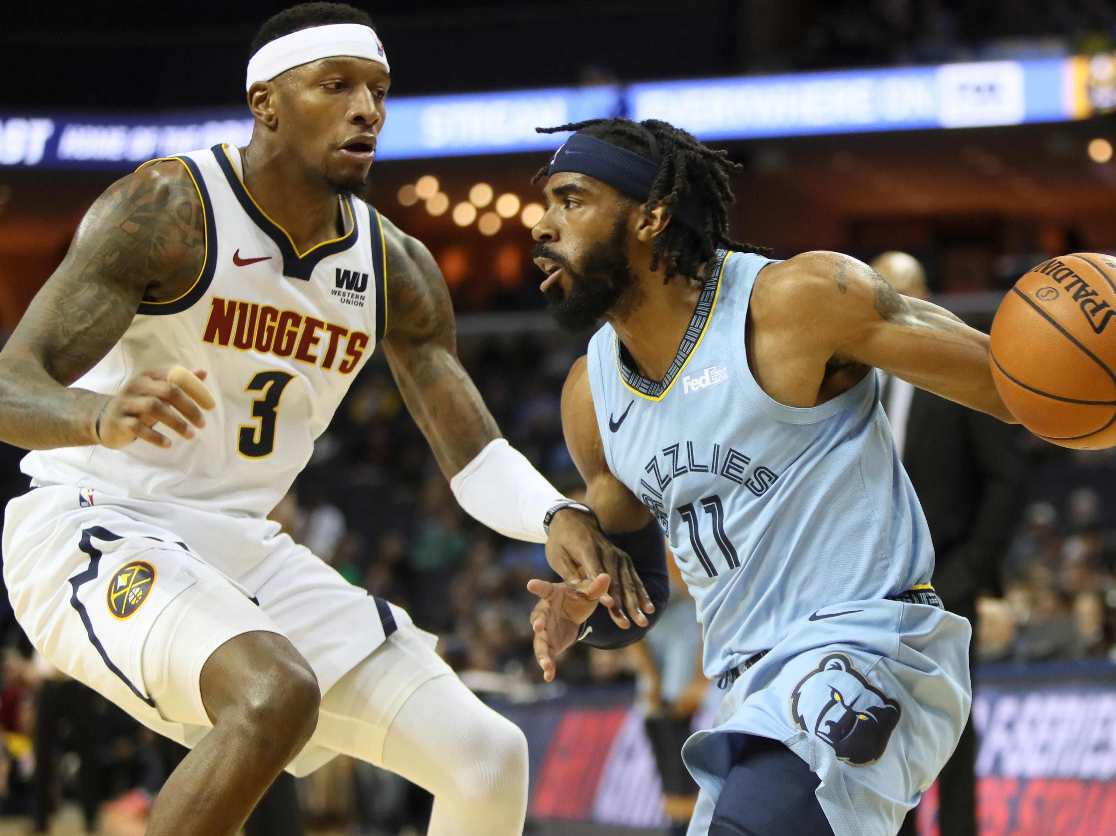 Memphis Grizzlies guard Mike Conley looks to get past Denver Nuggets forward Torrey Craig during their game at the FedExForum on Wednesday, November 7, 2018.