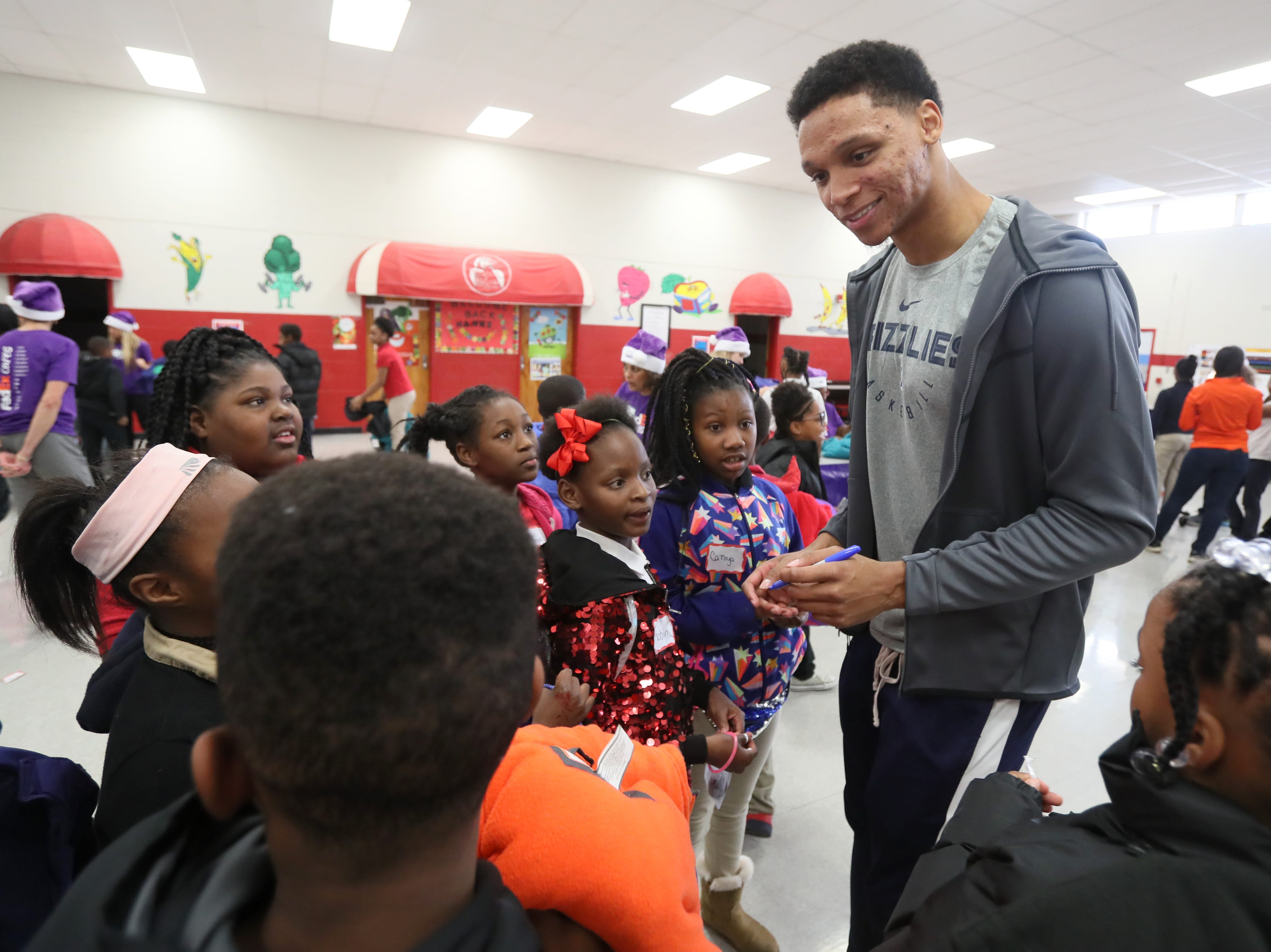 Memphis Grizzlies forward Ivan Rabb signs autographs for srudents as his team joins FedEx and Operation Warm to help surprise children with new coats at Hawkins Mill Elementary School on Thursday, Nov. 8, 2018.