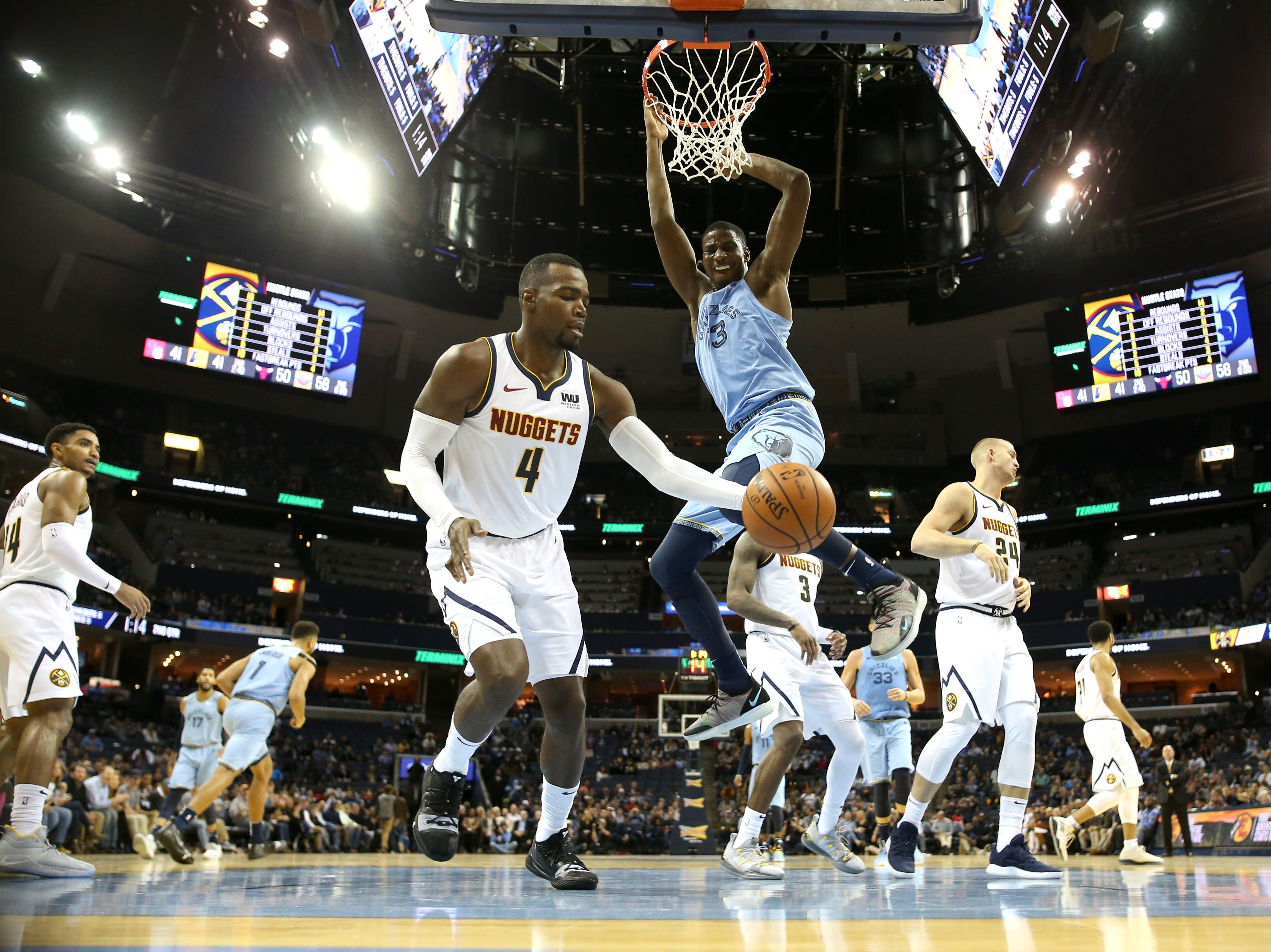 Memphis Grizzlies forward Jaren Jackson Jr. dunks the ball against Denver Nuggets forward Paul Millsap during their game at the FedExForum on Wednesday, November 7, 2018.