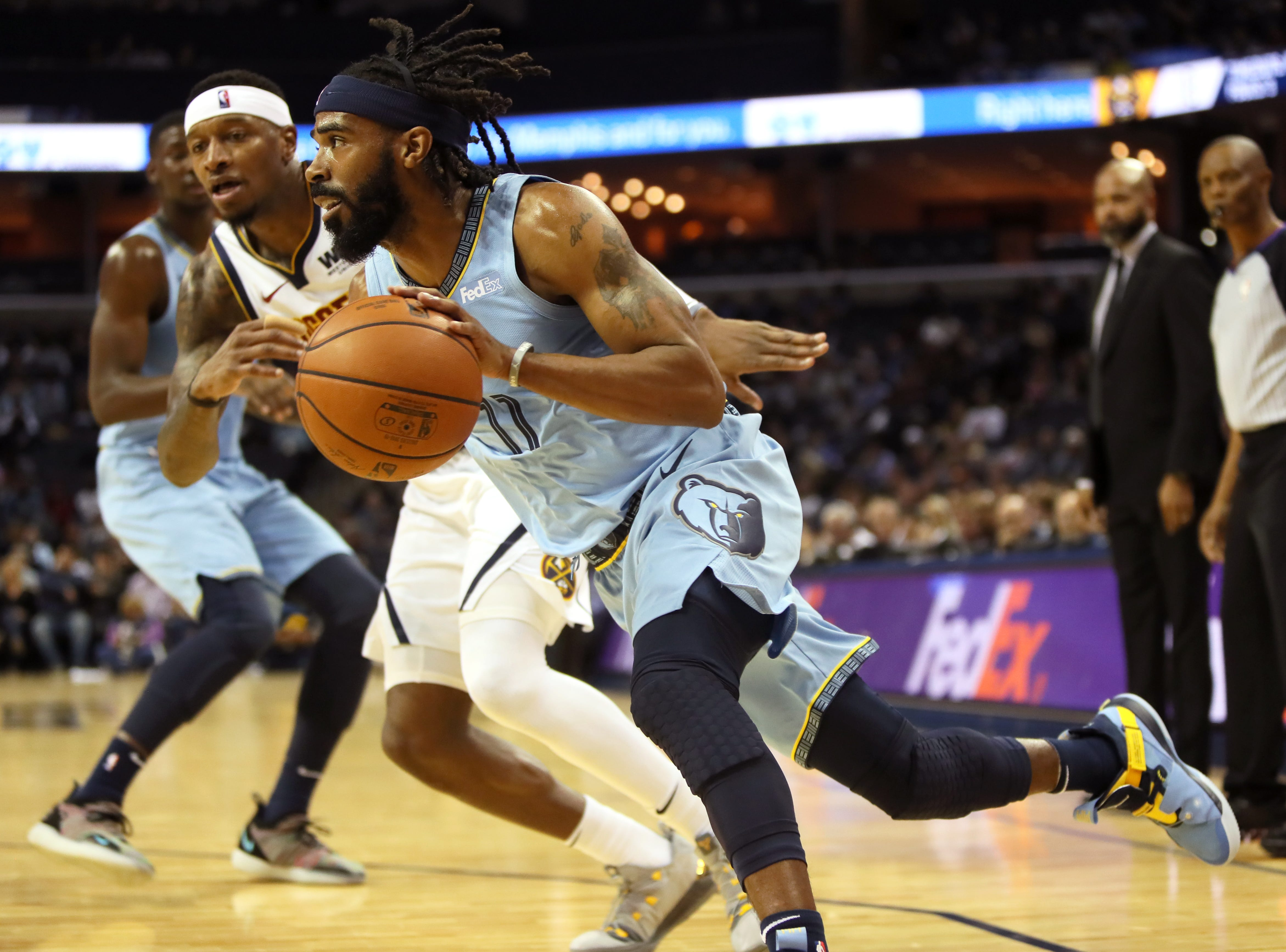 Memphis Grizzlies guard Mike Conley drives past Denver Nuggets forward Torrey Craig during their game at the FedExForum on Wednesday, November 7, 2018.