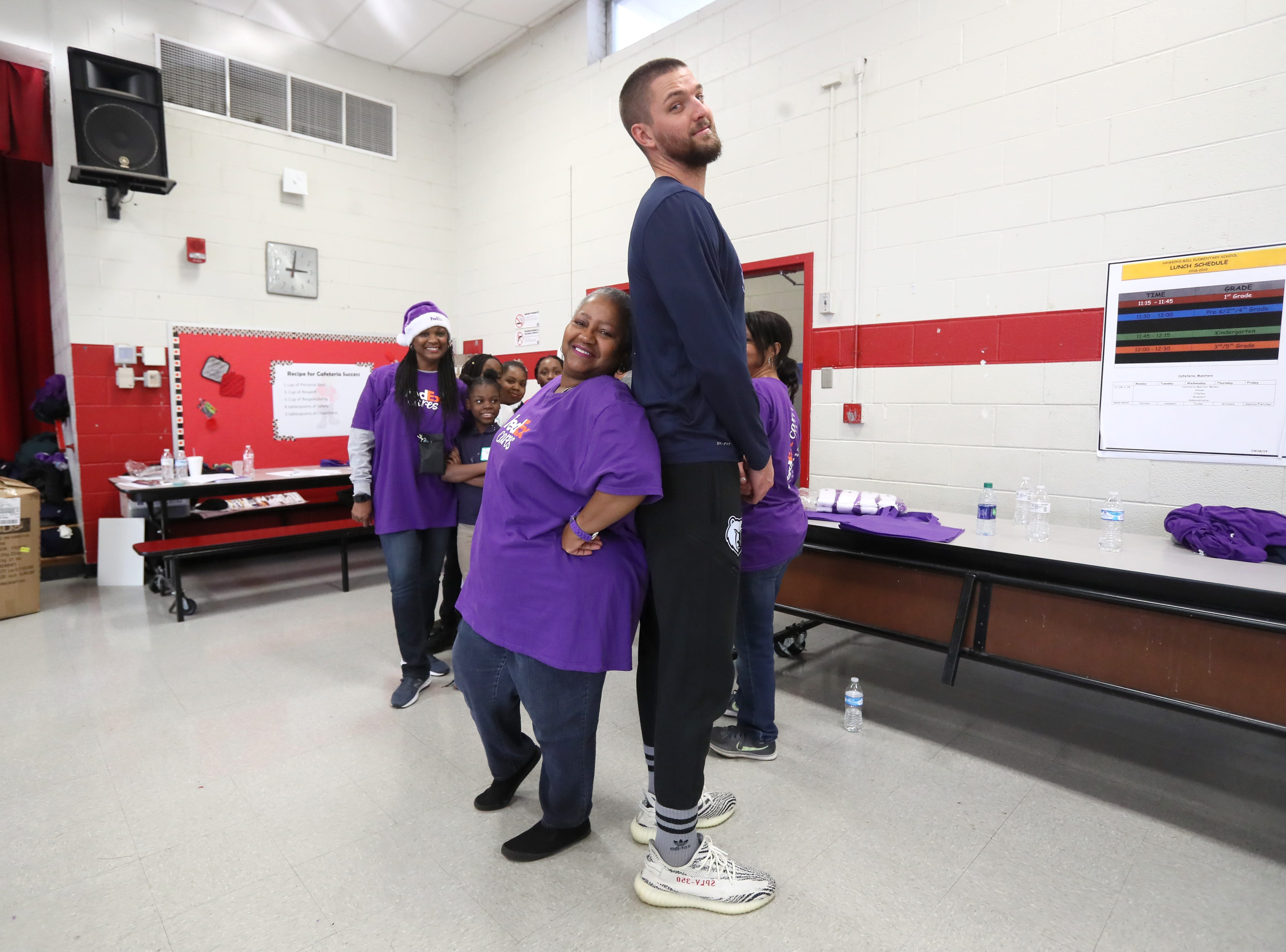 FedEx employee Beverly Goines measures up against Chandler Parsons as they join Operation Warm to surprise children with new coats at Hawkins Mill Elementary School on Thursday, Nov. 8, 2018.