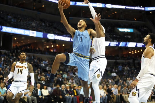 Memphis Grizzlies guard Kyle Anderson lays the ball up past Denver Nuggets forward Torrey Craig during their game at the FedExForum on Wednesday, November 7, 2018.