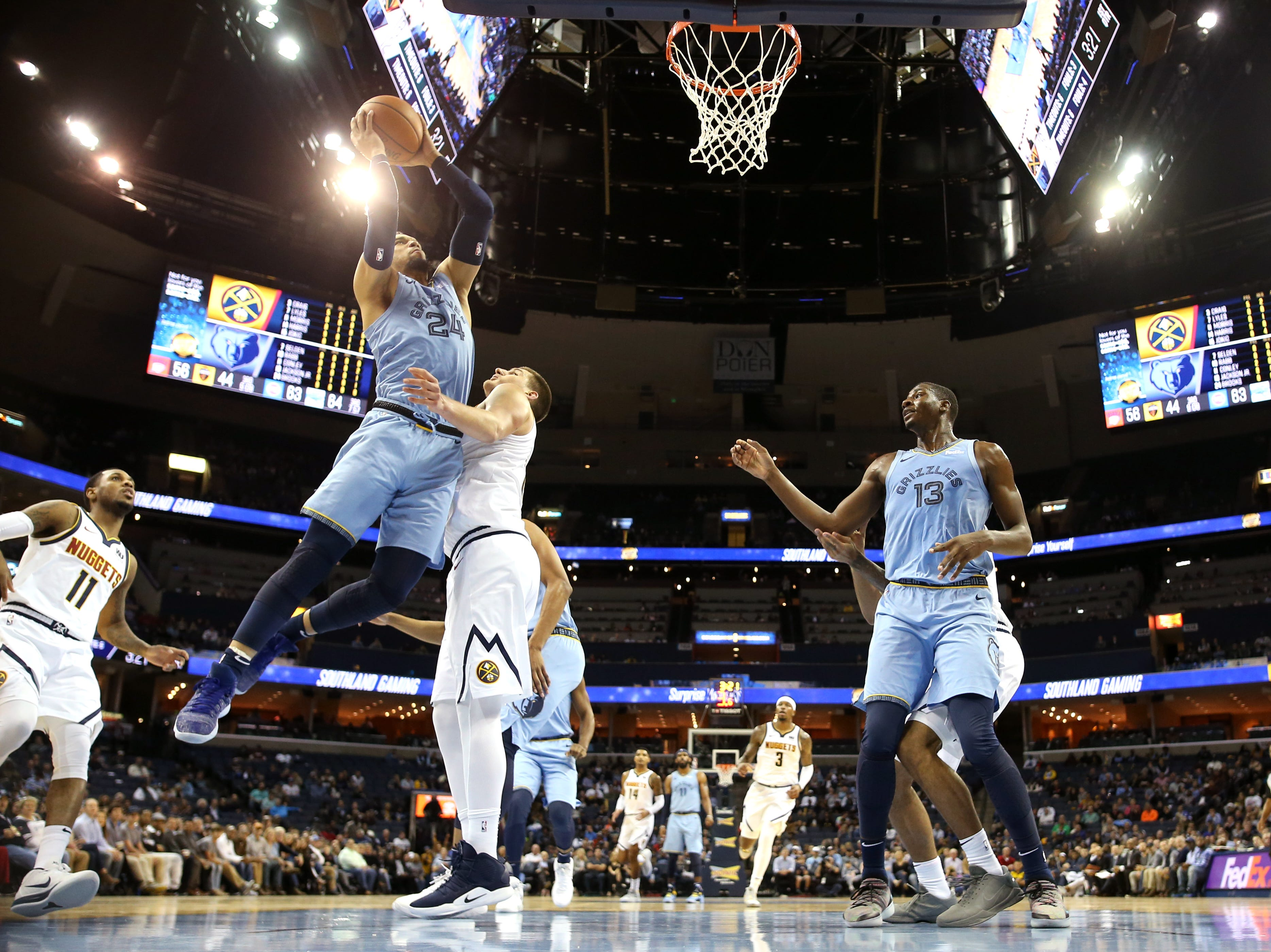 Memphis Grizzlies guard Dillon Brooks lays the ball up against Denver Nuggets center Nikola Jokic during their game at the FedExForum on Wednesday, November 7, 2018.