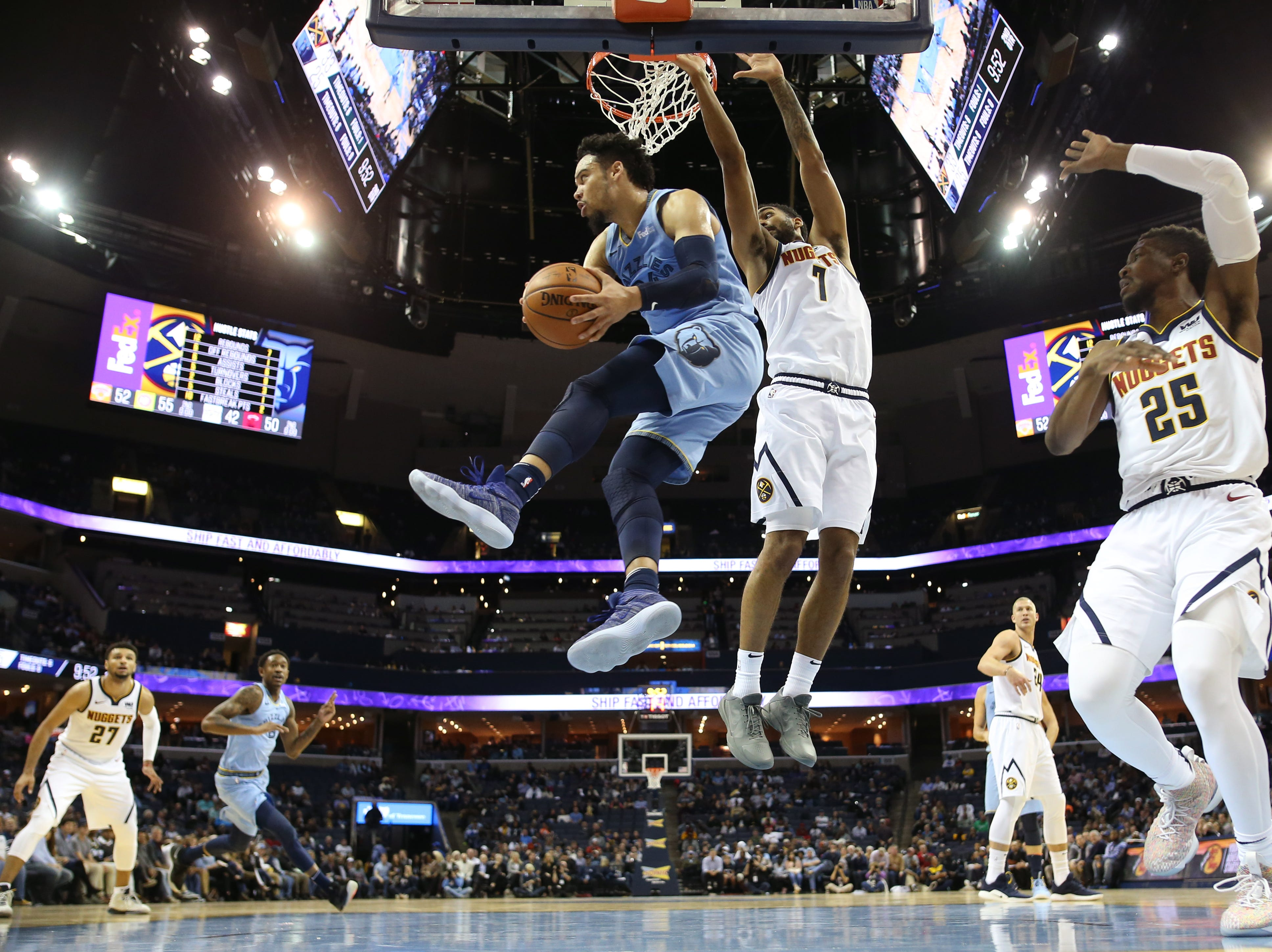 Memphis Grizzlies guard Dillon Brooks looks to pass the ball from the air past Denver Nuggets forward Trey Lyles during their game at the FedExForum on Wednesday, November 7, 2018.