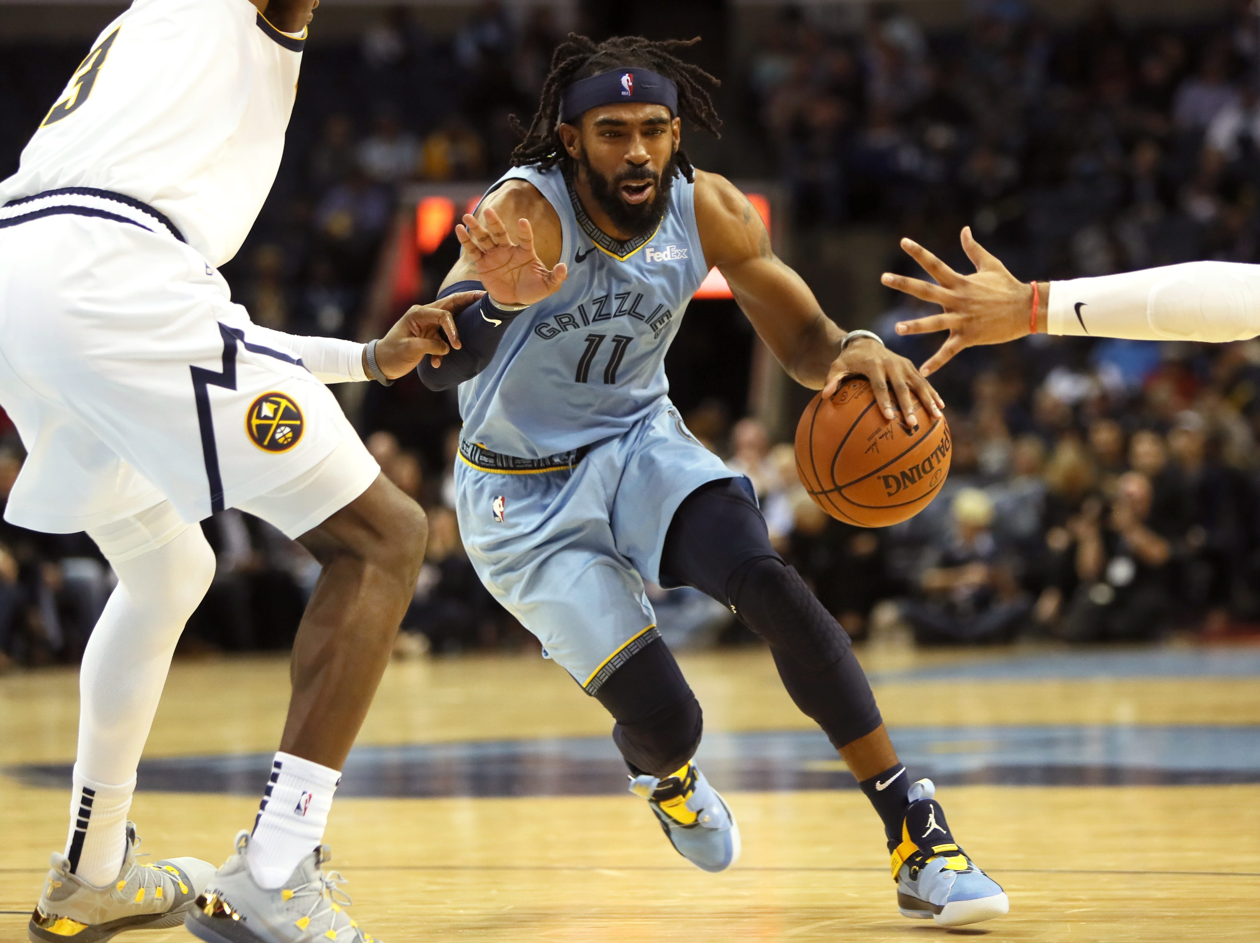 Memphis Grizzlies guard Mike Conley splits the defenders to drive in to the lane against the Denver Nuggets during their game at the FedExForum on Wednesday, November 7, 2018.