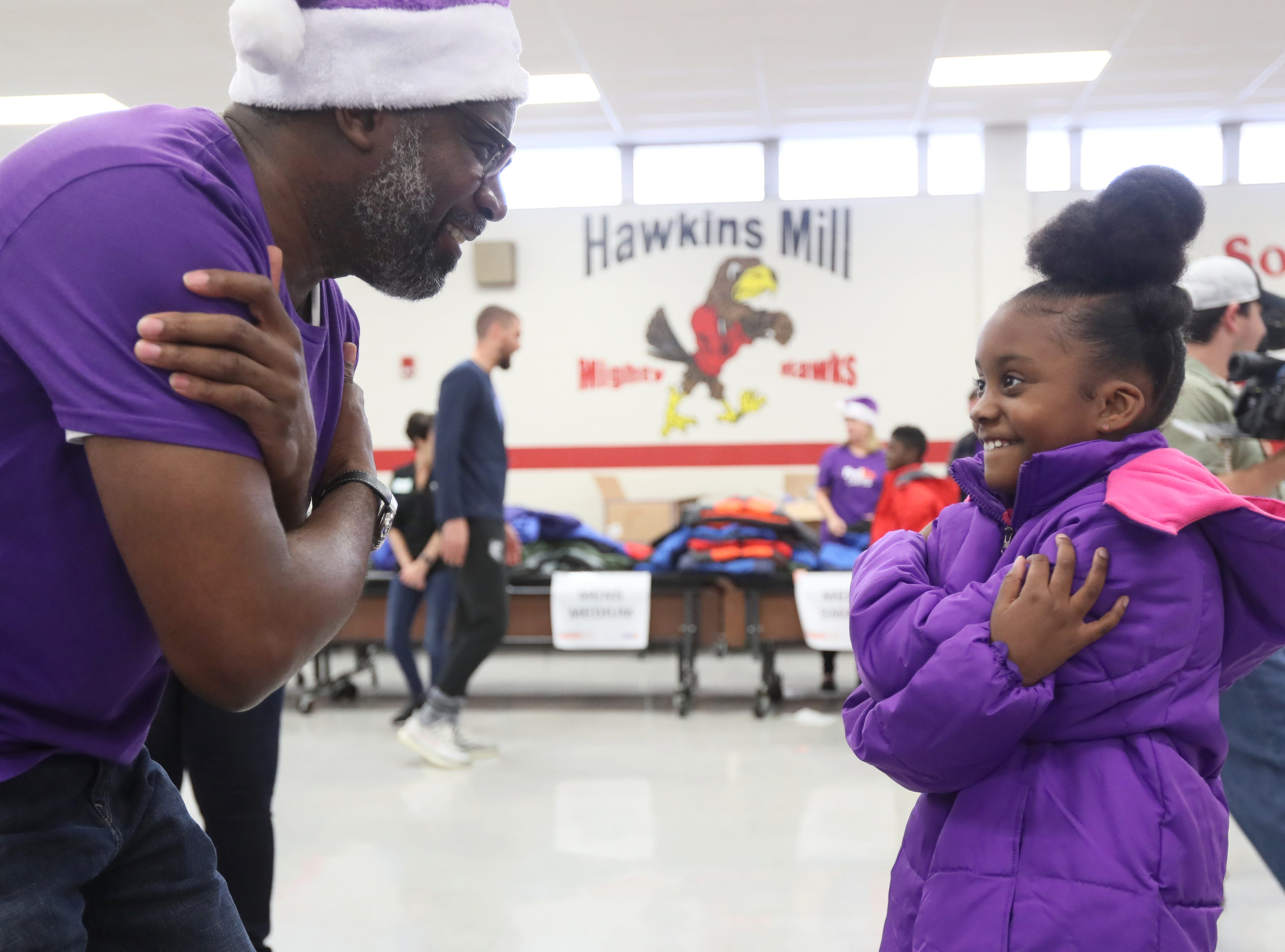 Brian Tabor helps Ambriella Watson, 9, try on a new coat as FedEx, the Memphis Grizzlies and Operation Warm surprise children with new winter wear at Hawkins Mill Elementary School on Thursday, Nov. 8, 2018.