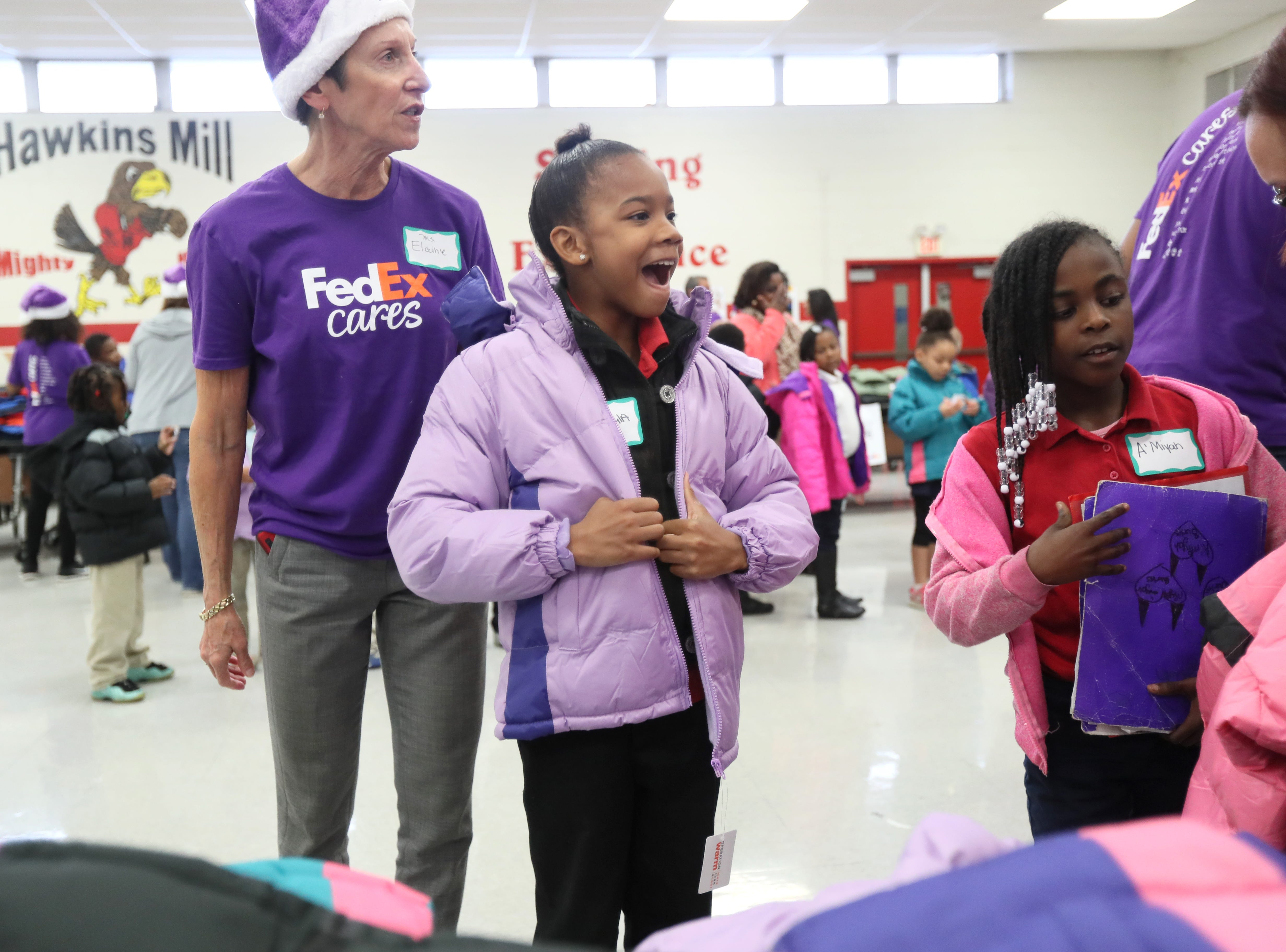 Markayla Thomas, 8, is fitted for a coat by FedEx office employee Elaine Cox as they join the Memphis Grizzlies and Operation Warm to surprise children with new winter wear at Hawkins Mill Elementary School on Thursday, Nov. 8, 2018.