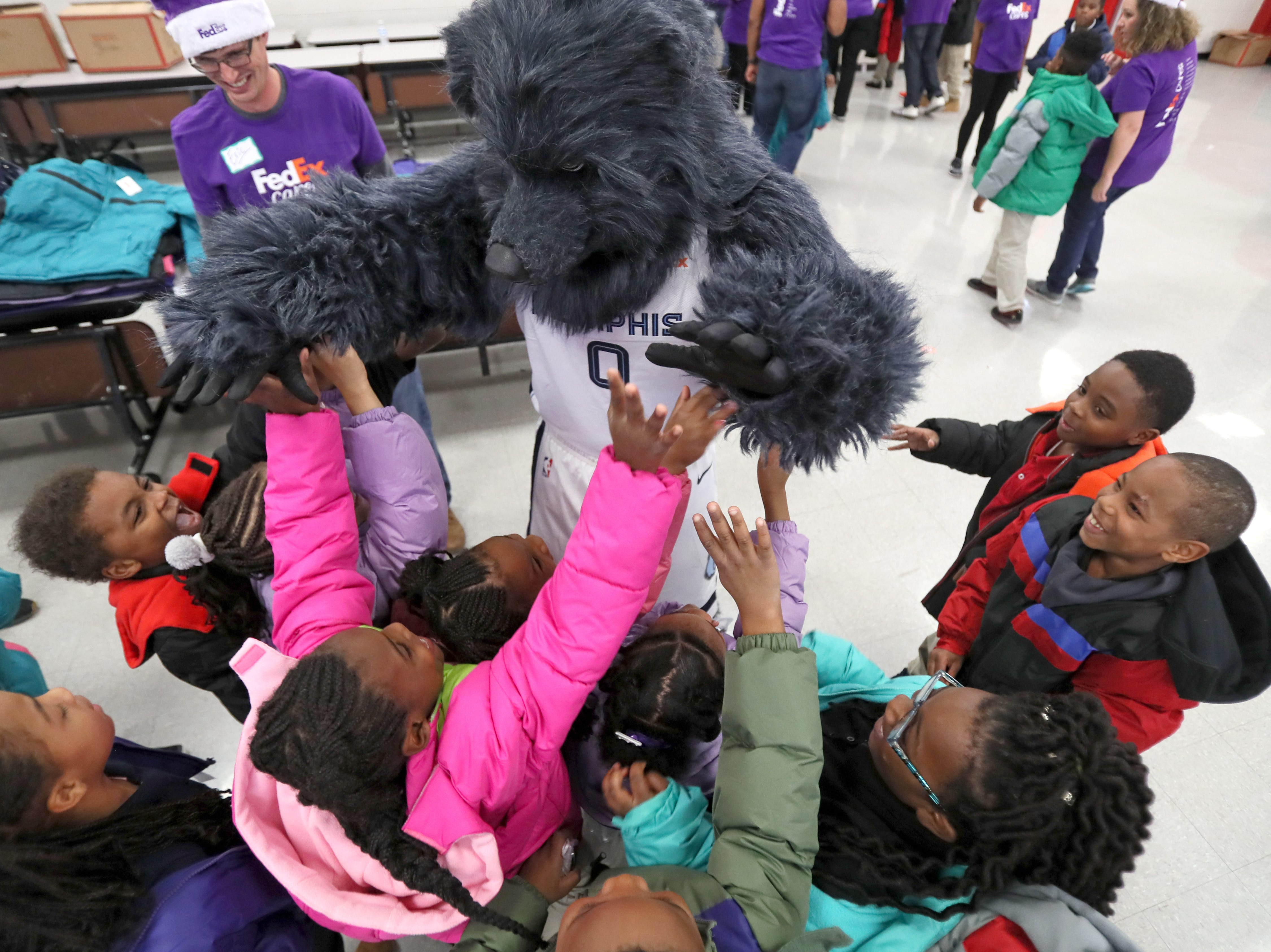 Memphis Grizzlies' mascott Grizz greets students as the team joins FedEx and Operation Warm to surprise children with new coats at Hawkins Mill Elementary School on Thursday, Nov. 8, 2018.