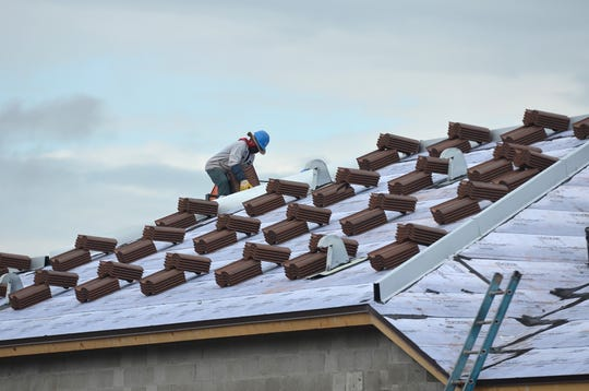 Workers load roof tile on a new home at Ave Maria in this file photo. Lance Shearer/Special to the Daily News