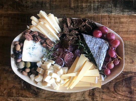 This cheese is anchored by a robiola covered in attractive gray vegetable ash from Boxcarr Handmade Cheese out of North Carolina, along with candied pecans from Treat, olives and fresh fruit.
