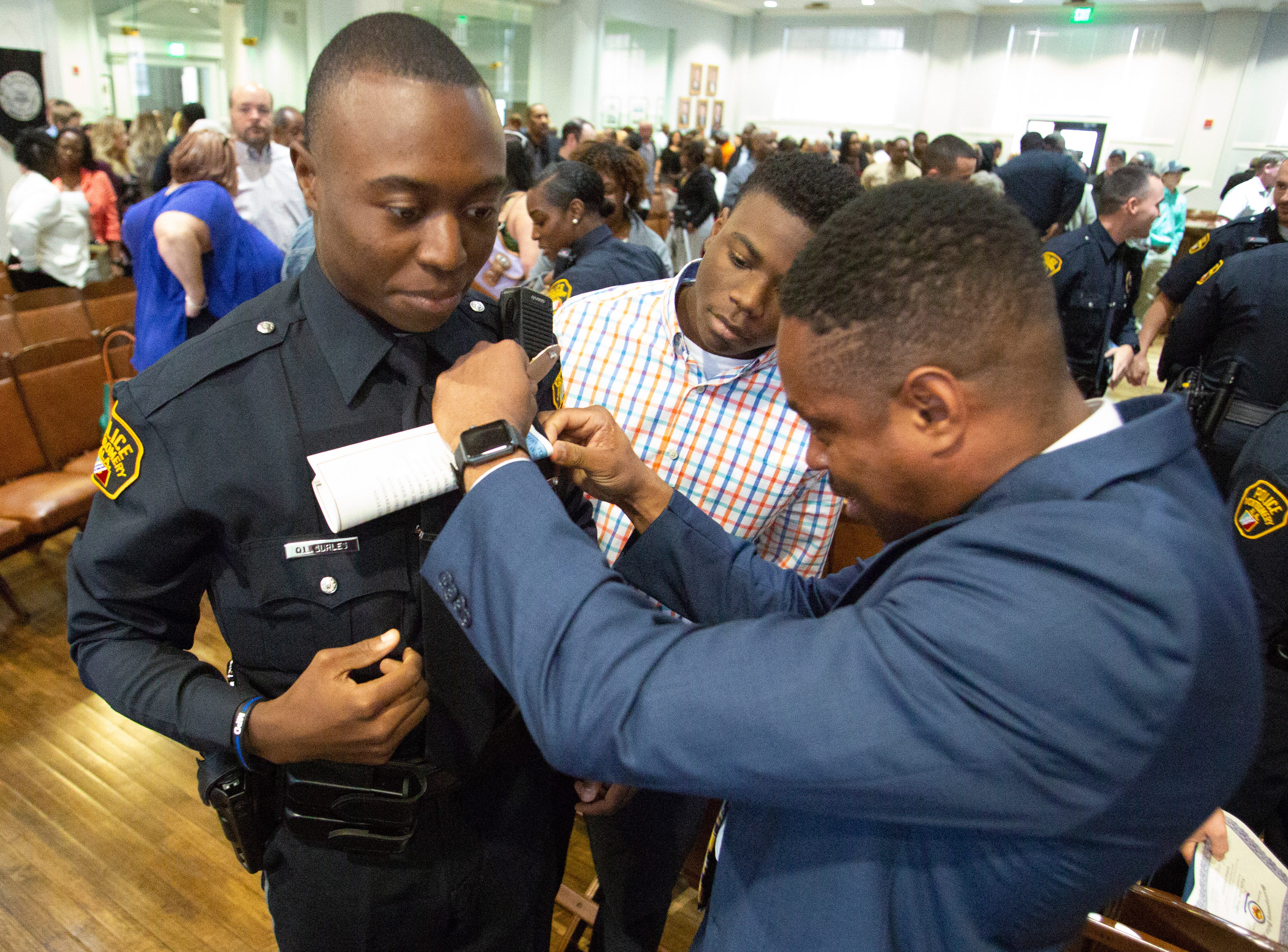 Montgomery police officer Quendarious Surles has his badge adjusted after graduating from the police academy.