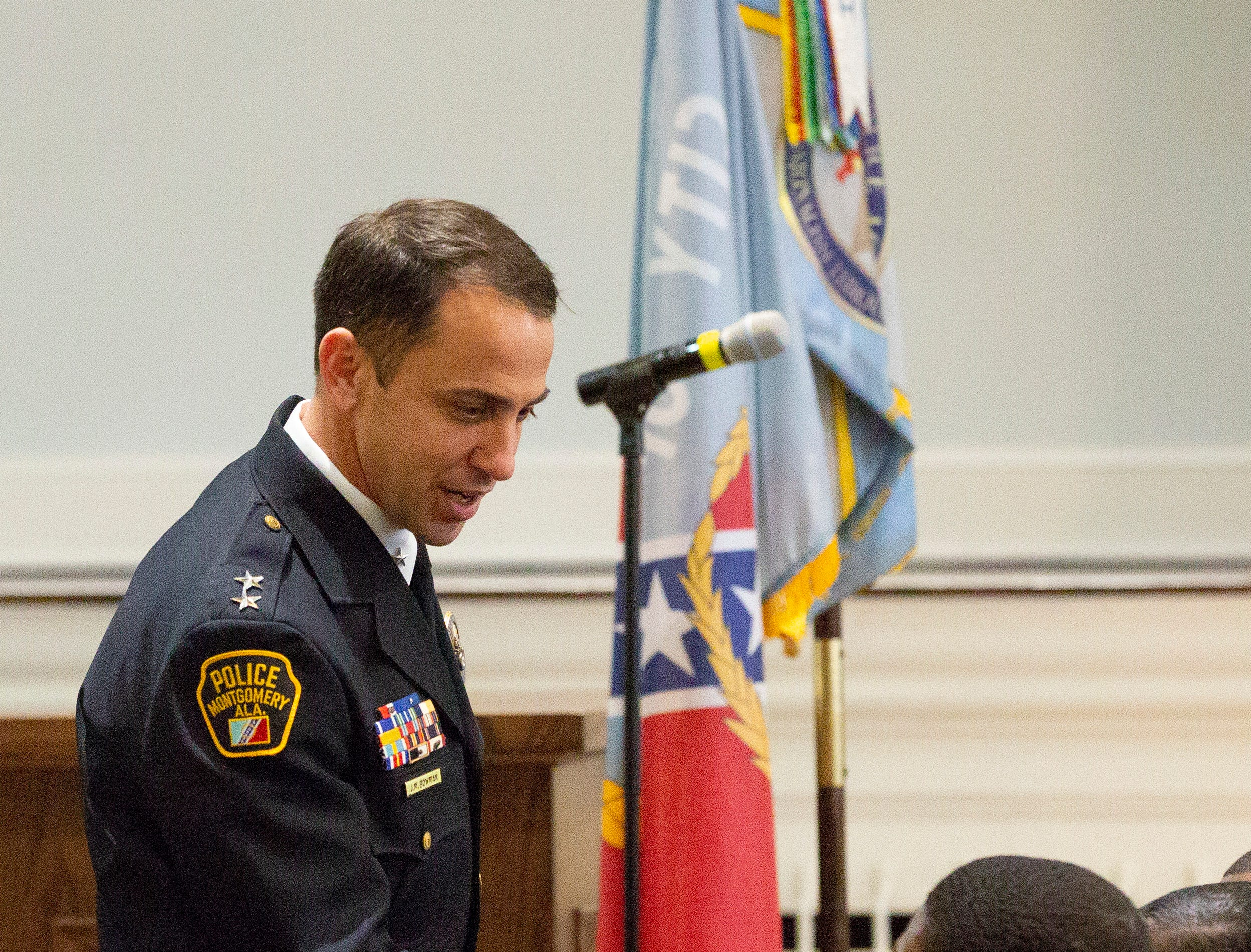 Montgomery police Chief of Staff John Bowman shakes hands with new recruits during a graduation ceremony.