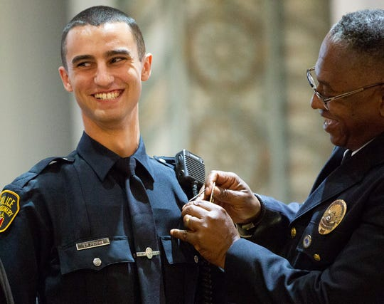 Montgomery police officer Thomas Ferrie smiles as Chief Ernest Finley pins his badge on his uniform.