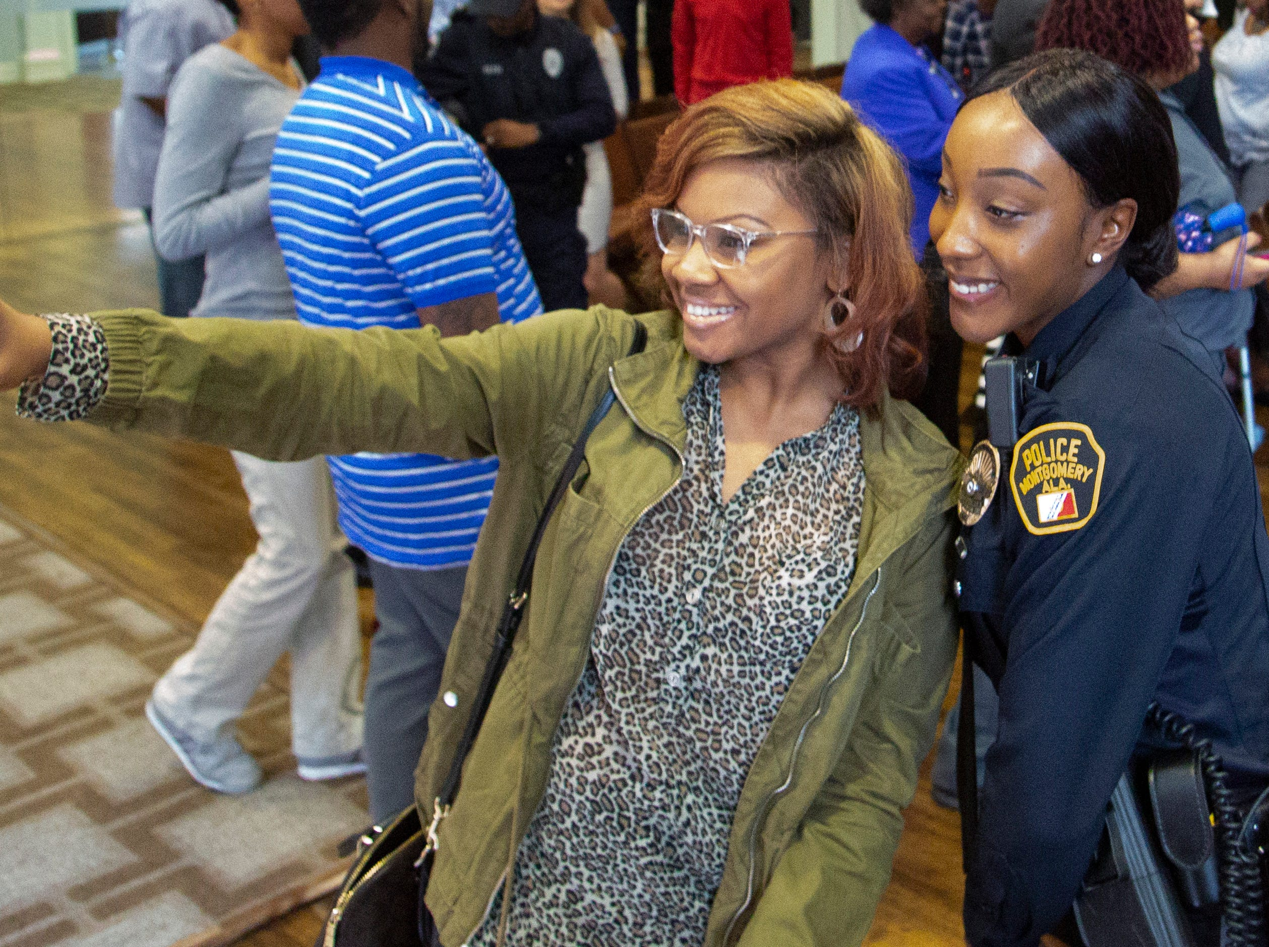 Montgomery police officer Alicia Terrell takes a selfie with a supporter after graduation.