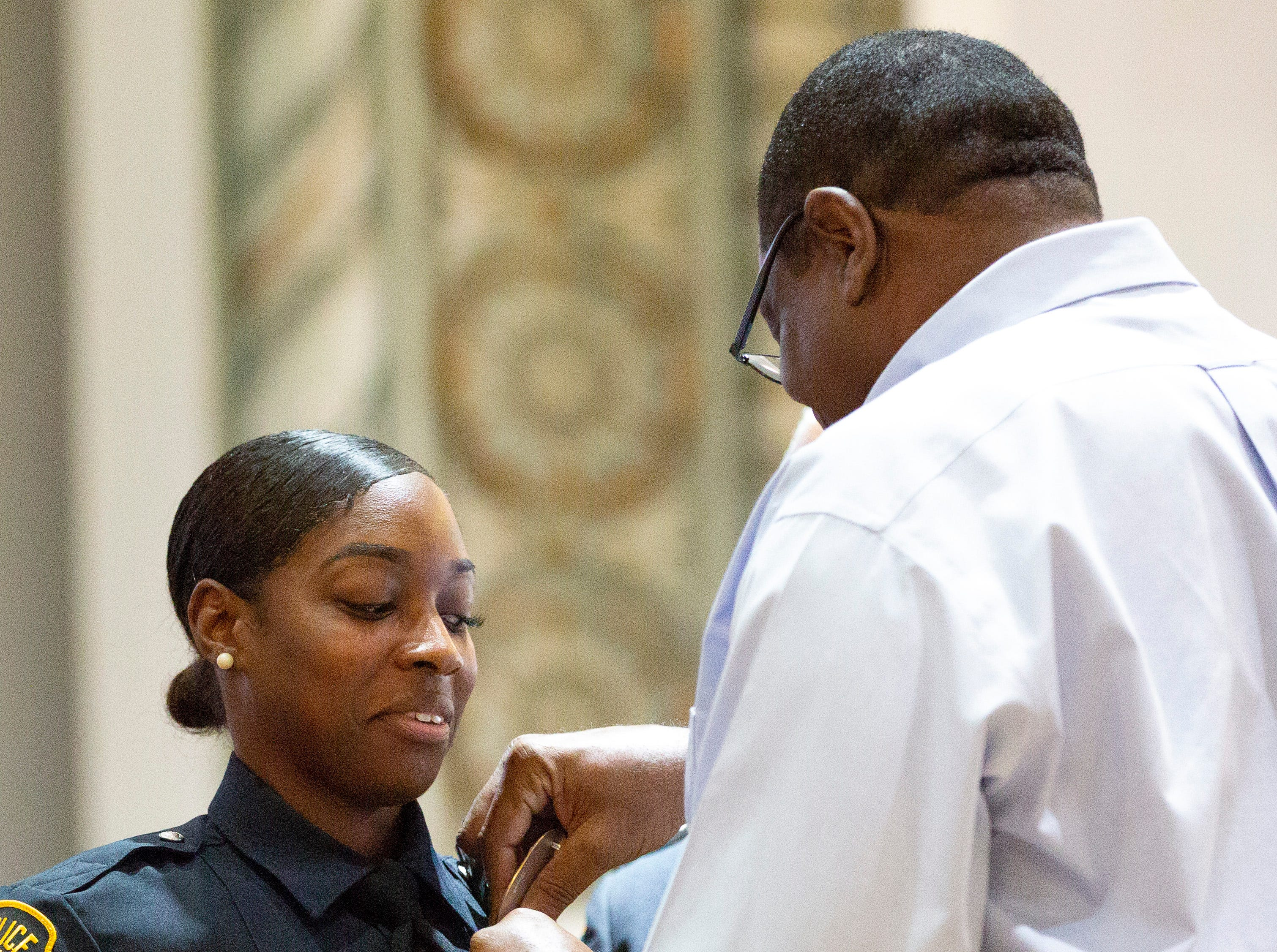 Montgomery police officer Tina Marie Jones watches hesitantly as her father pins her badge on her uniform.