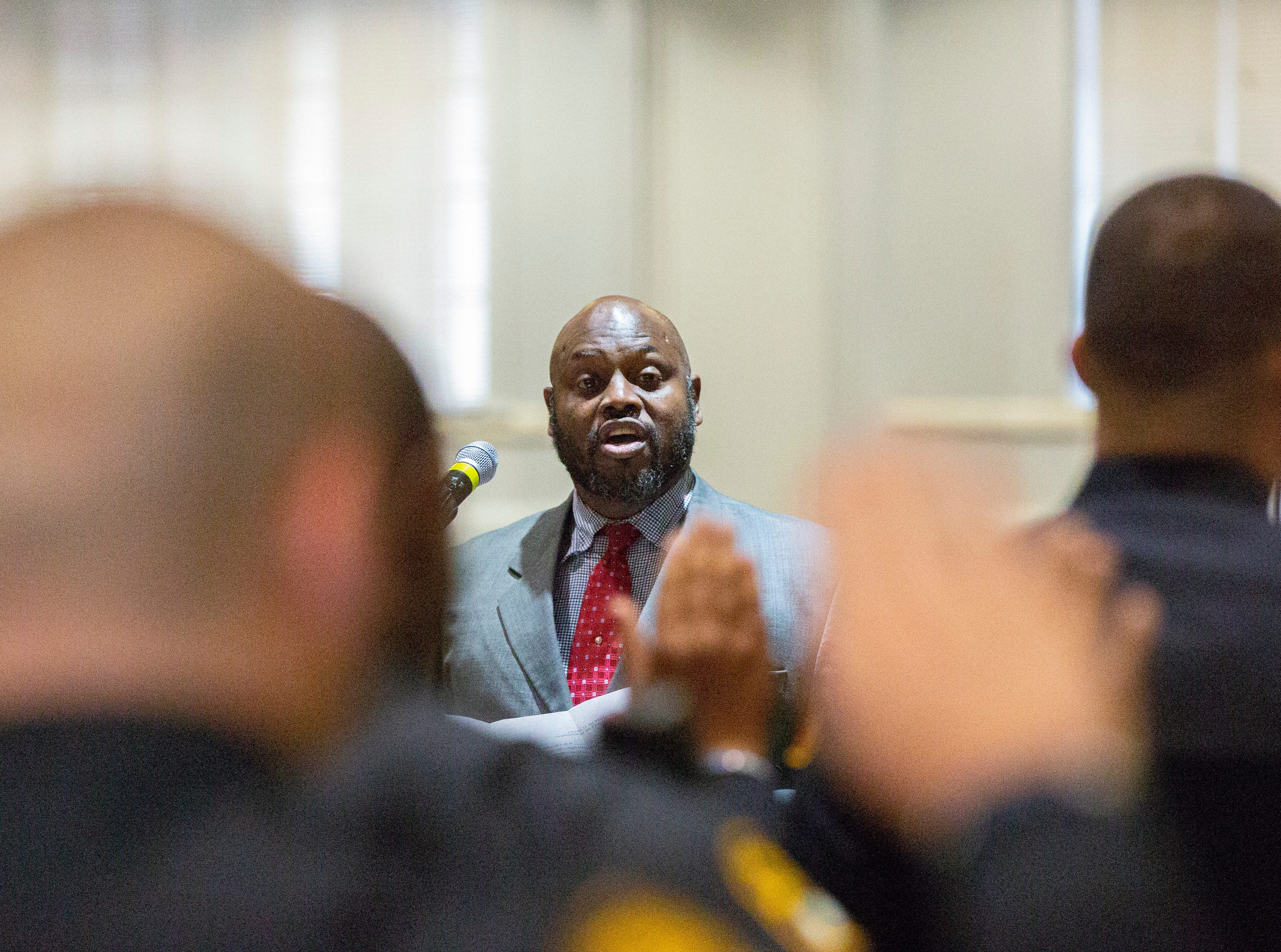 Judge Milton Westry gives 16 new Montgomery police officers their oaths during a graduation ceremony at City Hall.