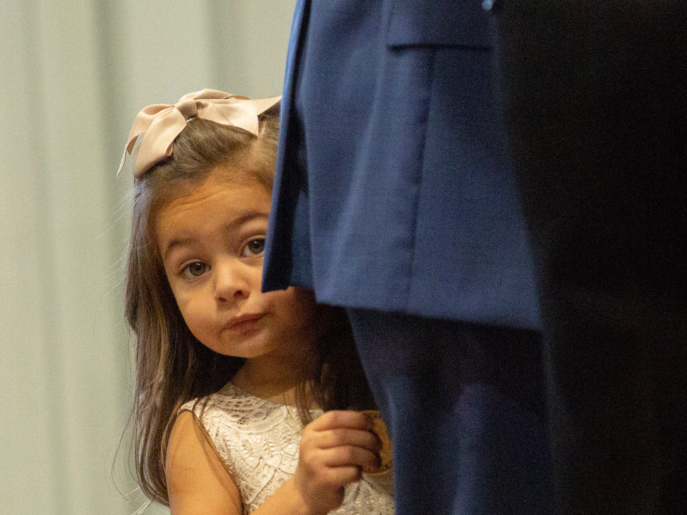 A young girl peeks out from behind her guardian during a police graduation ceremony.