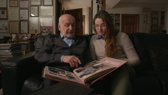 """Nicole Lehrman (right) looks at old photos with her grandfather Gabriel DeLobbe. DeLobbe's experiences with World War II will be shared through a Ball State student-produced documentary, """"Saboteur."""""""