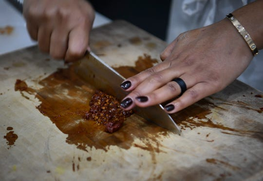 Chef Charity Morgan, wife of Titans linebacker Derrick Morgan chops chipotle peppers as she prepares vegan meals for about a dozen of her husband's teammates  Friday, Nov. 2, 2018, in Nashville, Tenn.