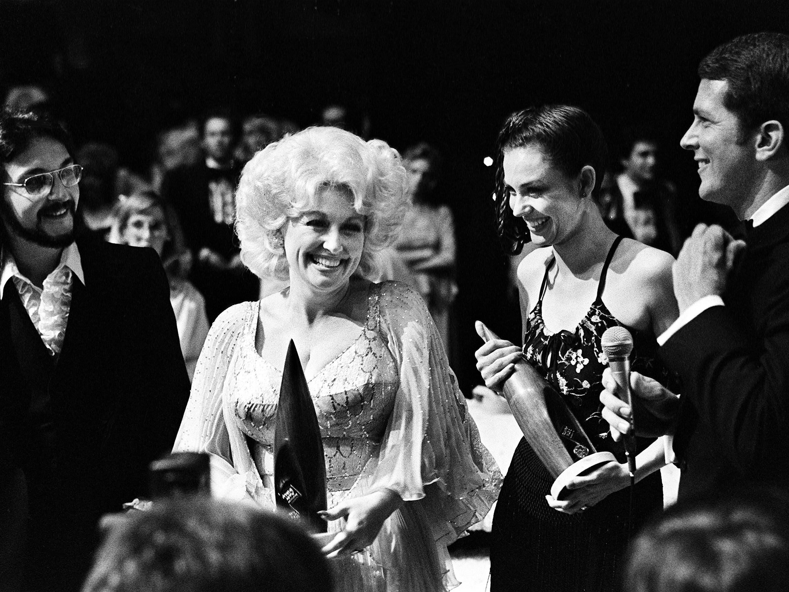 Entertainer of the Year winner Dolly Parton, second from left, talks with Female Vocalist of the Year winner Crystal Gayle before being interviewed backstage at the 12th annual CMA Awards show at the Grand Ole Opry House on Oct. 9, 1978.