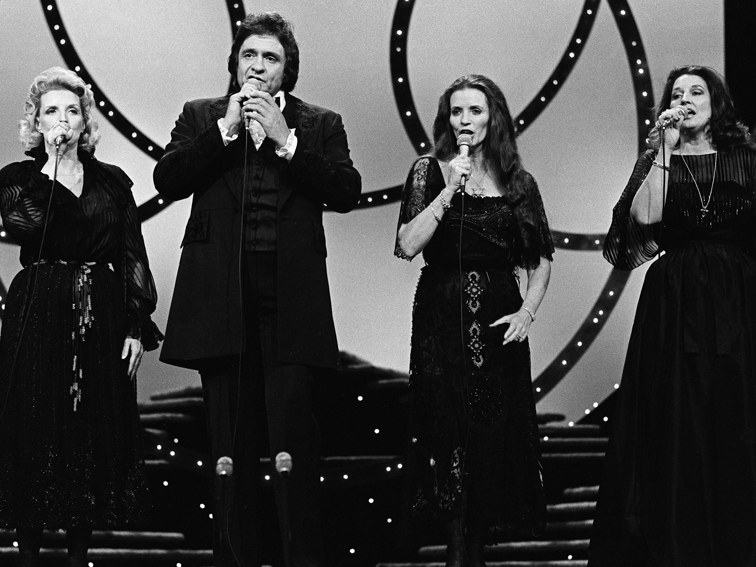 Host Johnny Cash performs with the Carter Family members Helen, left, wife June Carter Cash and Anita during the 12th annual CMA Awards show at the Grand Ole Opry House on Oct. 9, 1978.