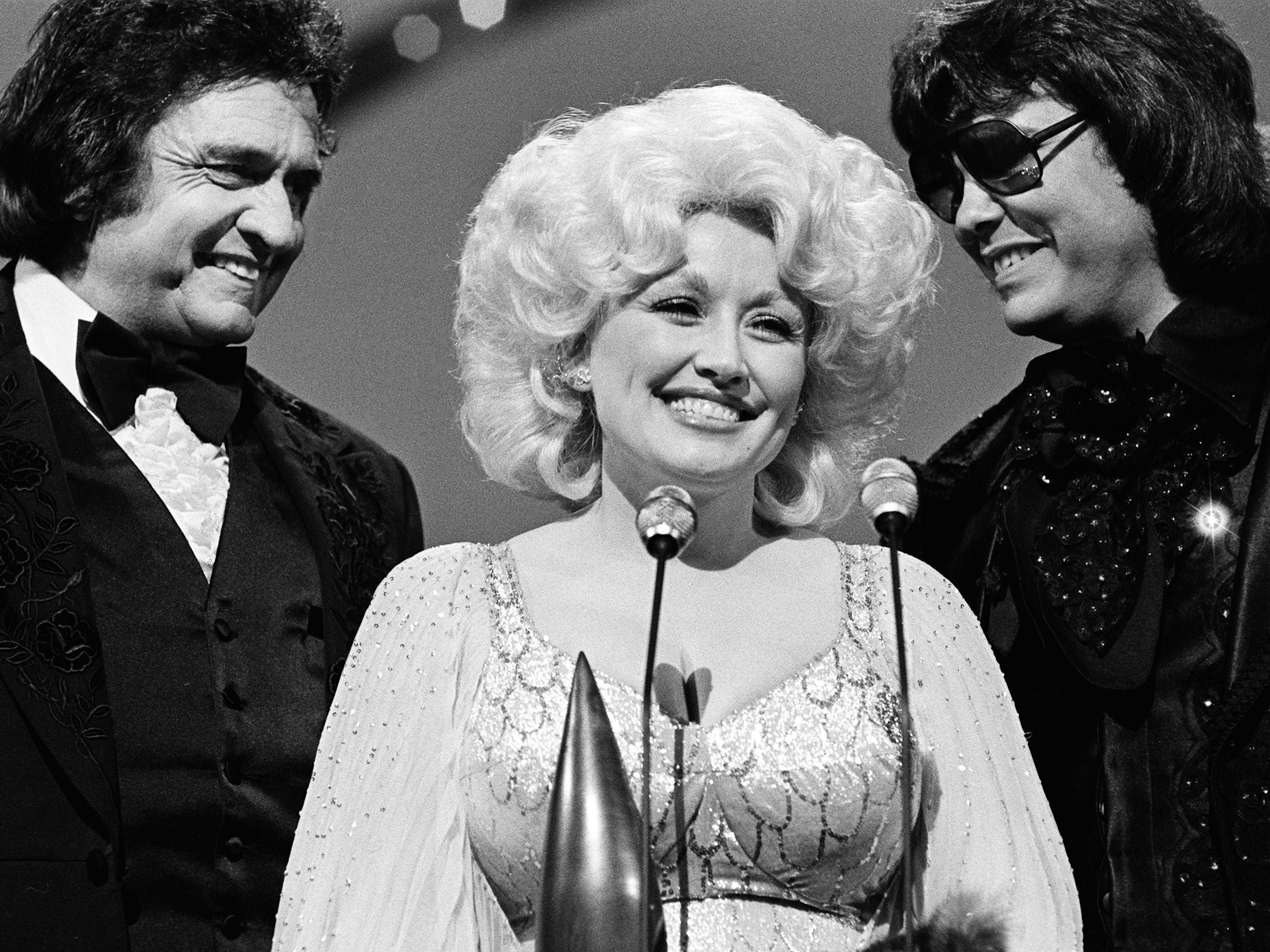 Dolly Parton accepts the Entertainer of the Year award during the 12th annual CMA Awards show Oct. 9, 1978, as presenters Johnny Cash, left, and Ronnie Milsap stand by.