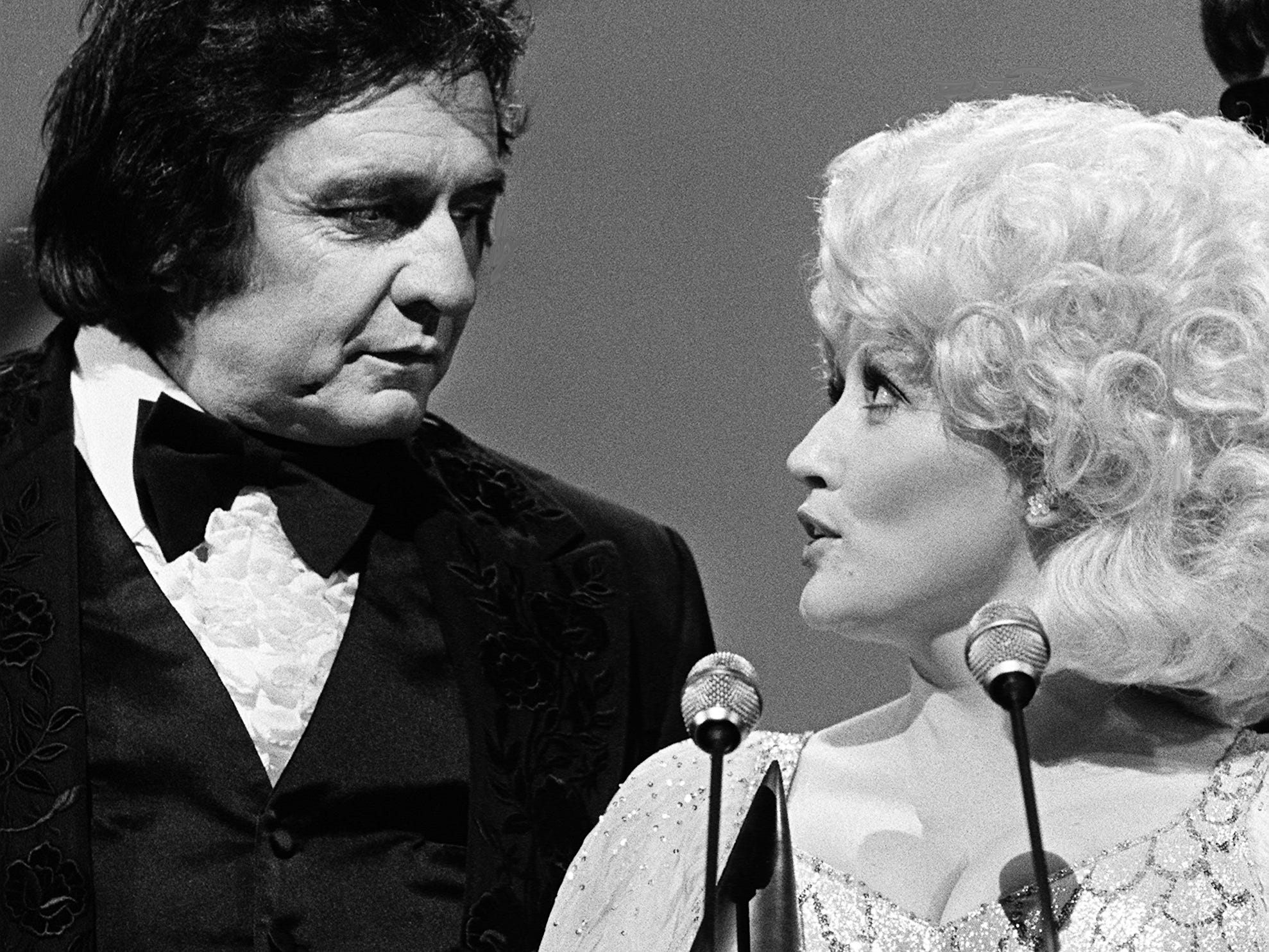 Dolly Parton speaks after winning the Entertainer of the Year award during the 12th annual CMA Awards show at the Grand Ole Opry House on Oct. 9, 1978. Looking on is presenter and host Johnny Cash.