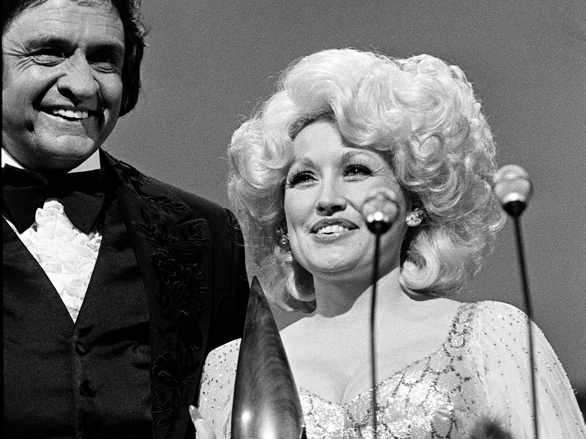 Dolly Parton accepts the Entertainer of the Year award during the 12th annual CMA Awards show Oct. 9, 1978, as presenter and host Johnny Cash looks on.