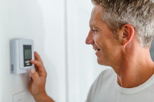 Smiling Man Adjusting Thermostat On Home Heating System