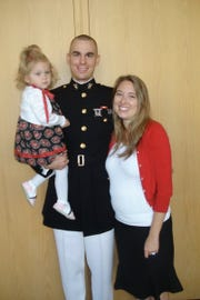 Aaron Dorn stands with his wife, Erin, and their daughter, Abigail, who wore a homemade Marine Corps dress, at graduation from Marines basic school at a base in Quantico, Va., in October 2009.