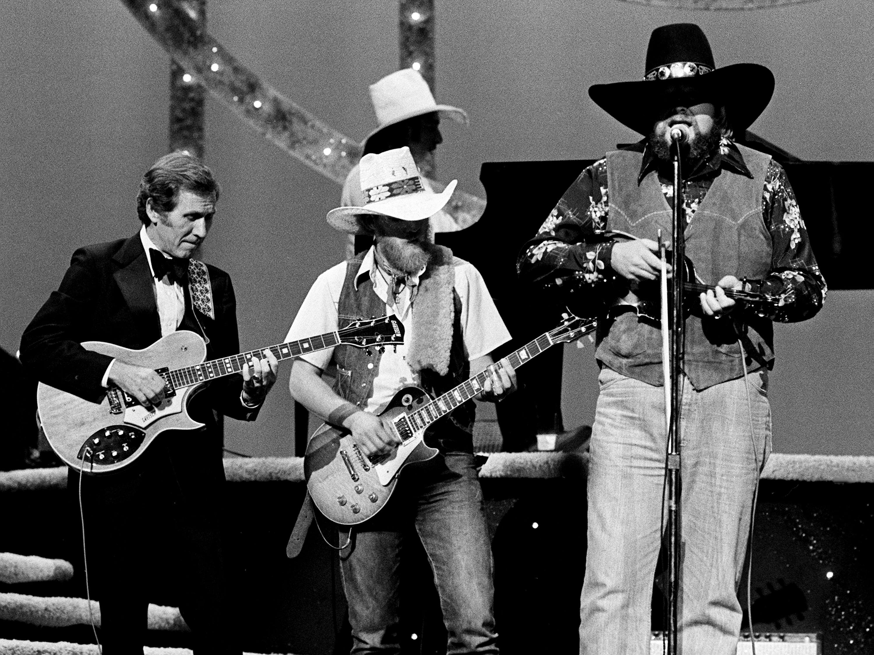 Chet Atkins, left, joins Charlie Daniels, right, and his band as they perform during the 12th annual CMA Awards show at the Grand Ole Opry House on Oct. 9, 1978.