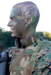 Aaron Dorn wears camo paint and a bulletproof vest before a warfare tactics training exercise at the Marine Corps base in Quantico, Va., in 2009.